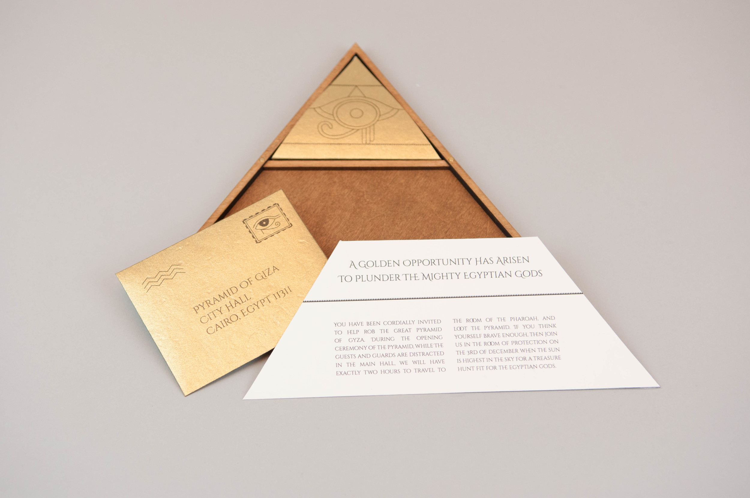 The inside of the invite is stained a rich brown, and reveals a note, an envelope, a key to decipher the code, all of which are printed on gold paper to mimic the front