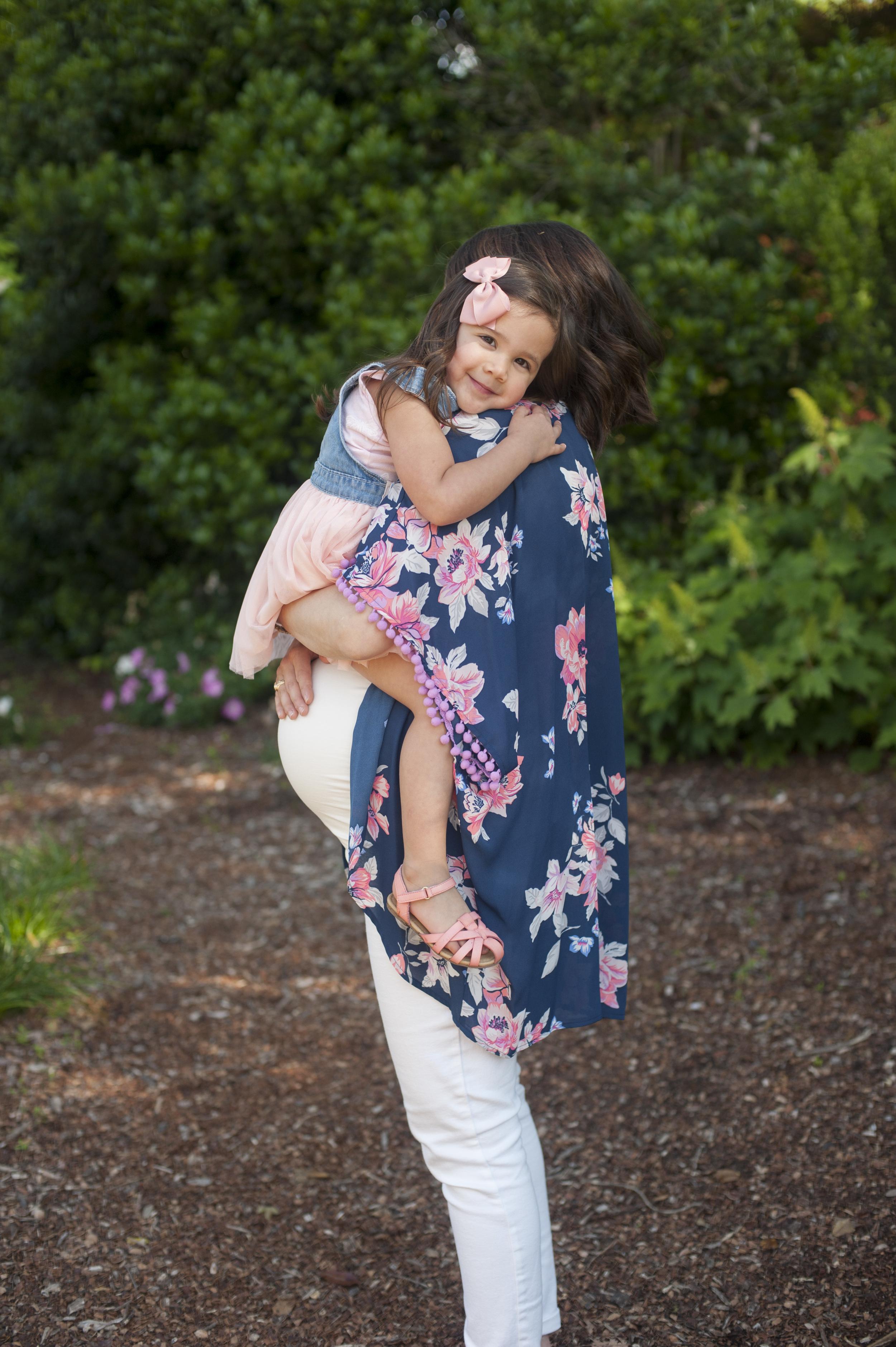 Big sister cuddling mom. Maternity photo at the Dallas Arboretum.