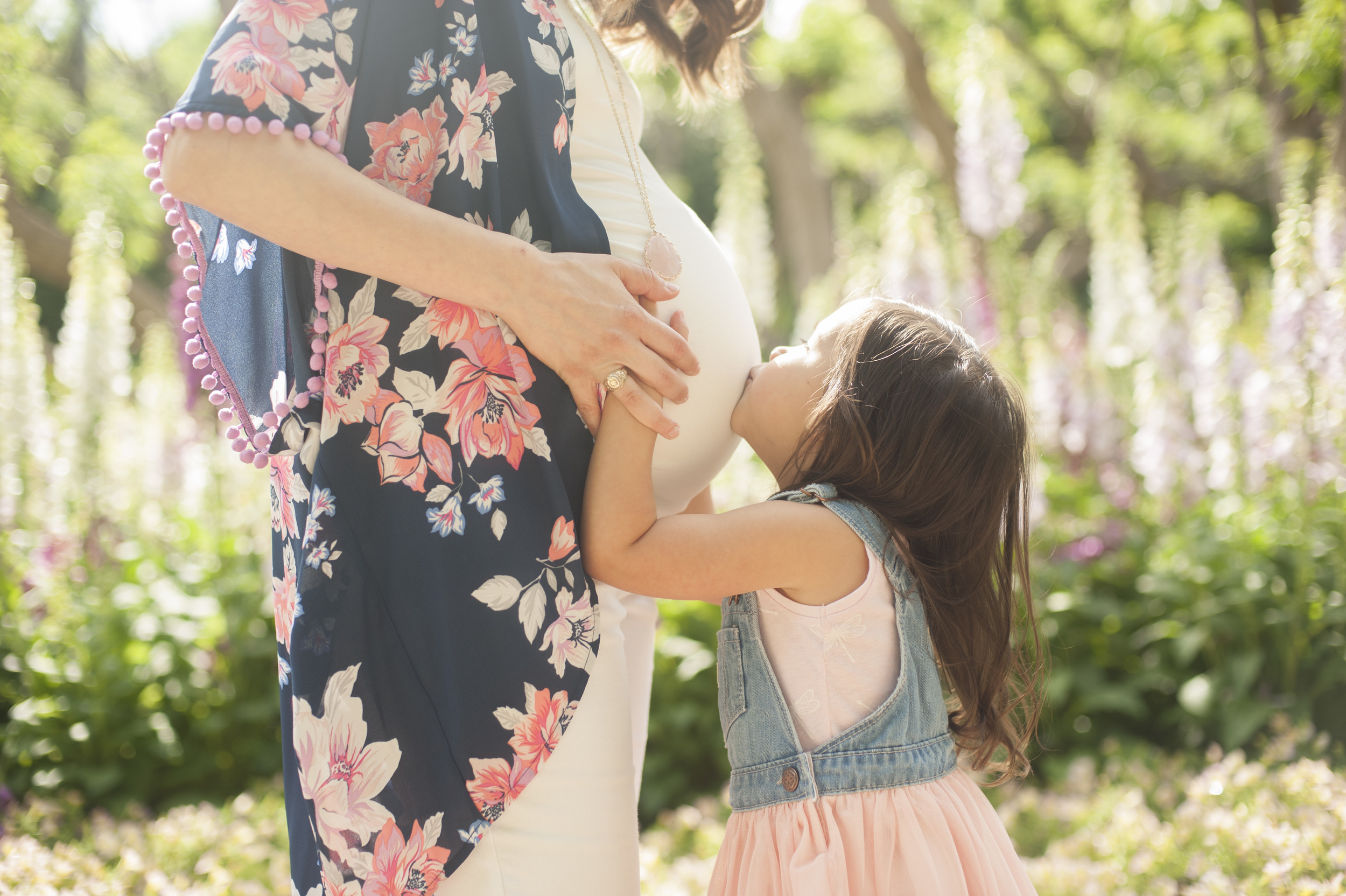 Big sister kissing her mother's pregnant belly. Maternity photo at the Dallas Arboretum.