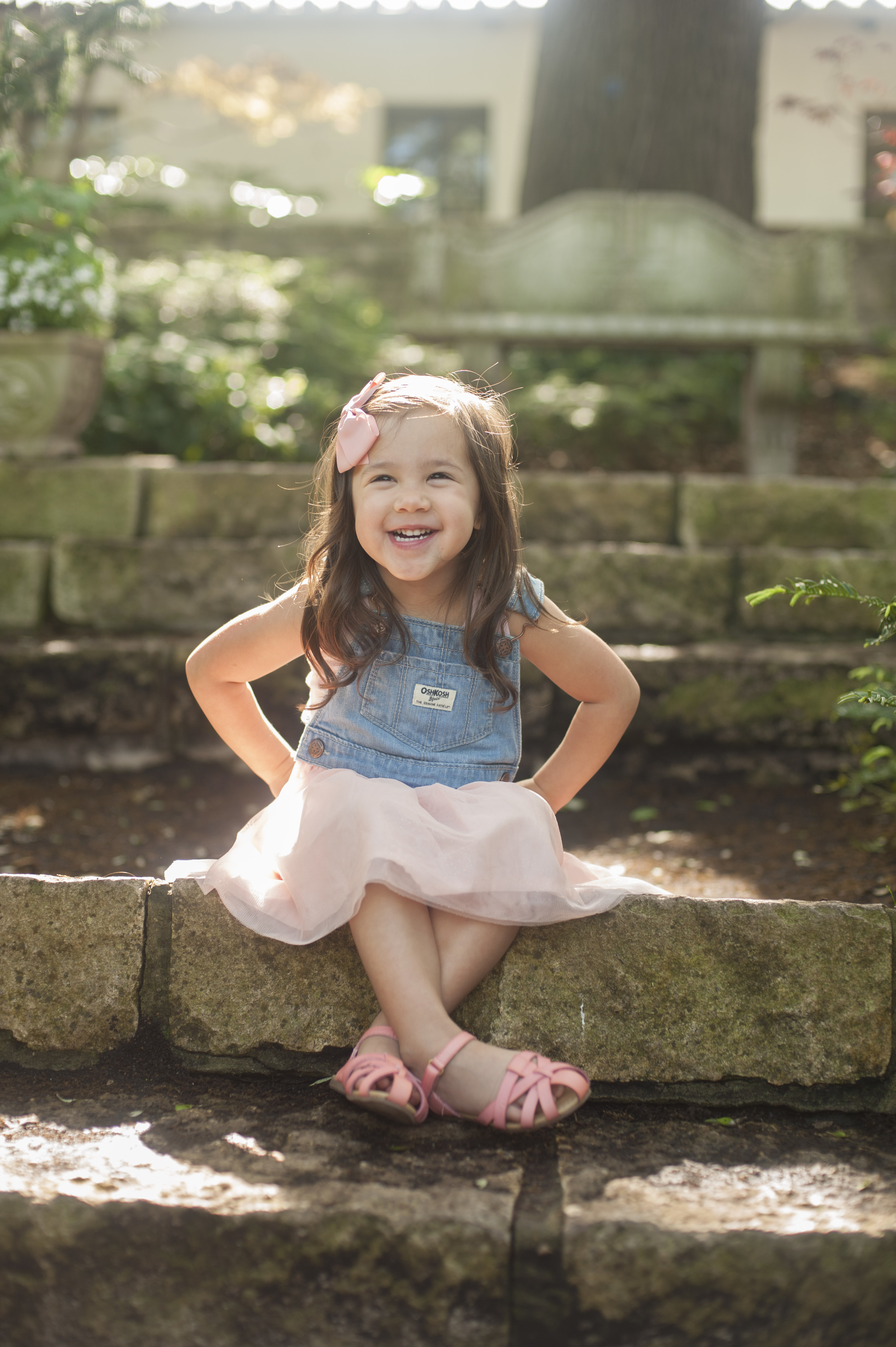 Sassy toddler sitting on stone steps. Childrens portrait at the Dallas Arboretum.