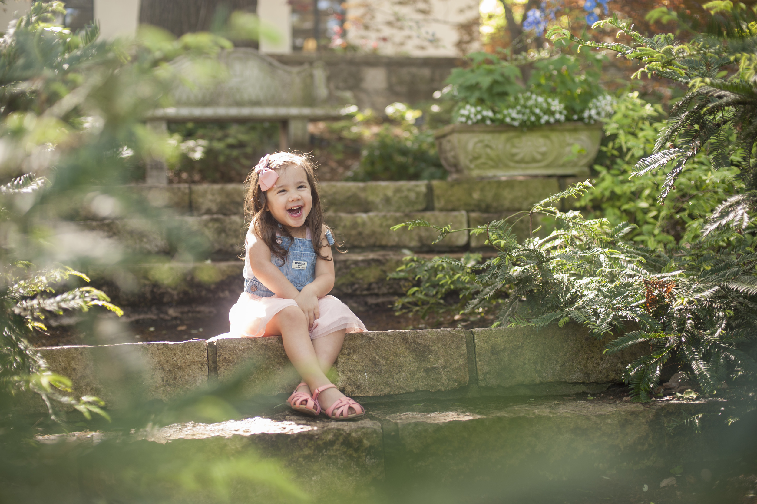 Toddler smiling amidst the greenery. Childrens portraits at the Dallas Arboretum.