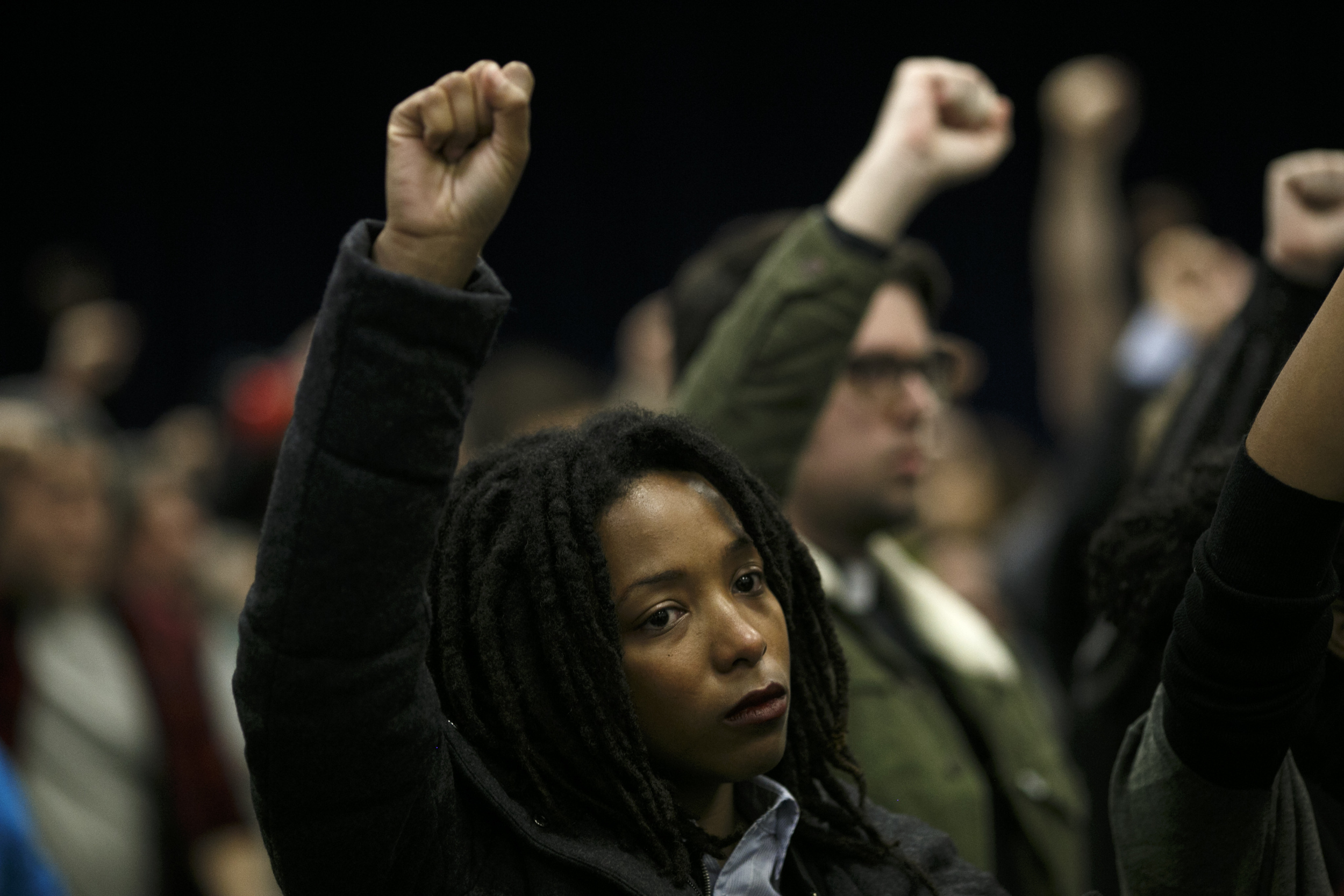 Attendees raise their fists in protest during the November Police Board Meeting at the Chicago Public Safety Headquarters on November 19, 2015 (Jonathan Gibby/City Bureau)