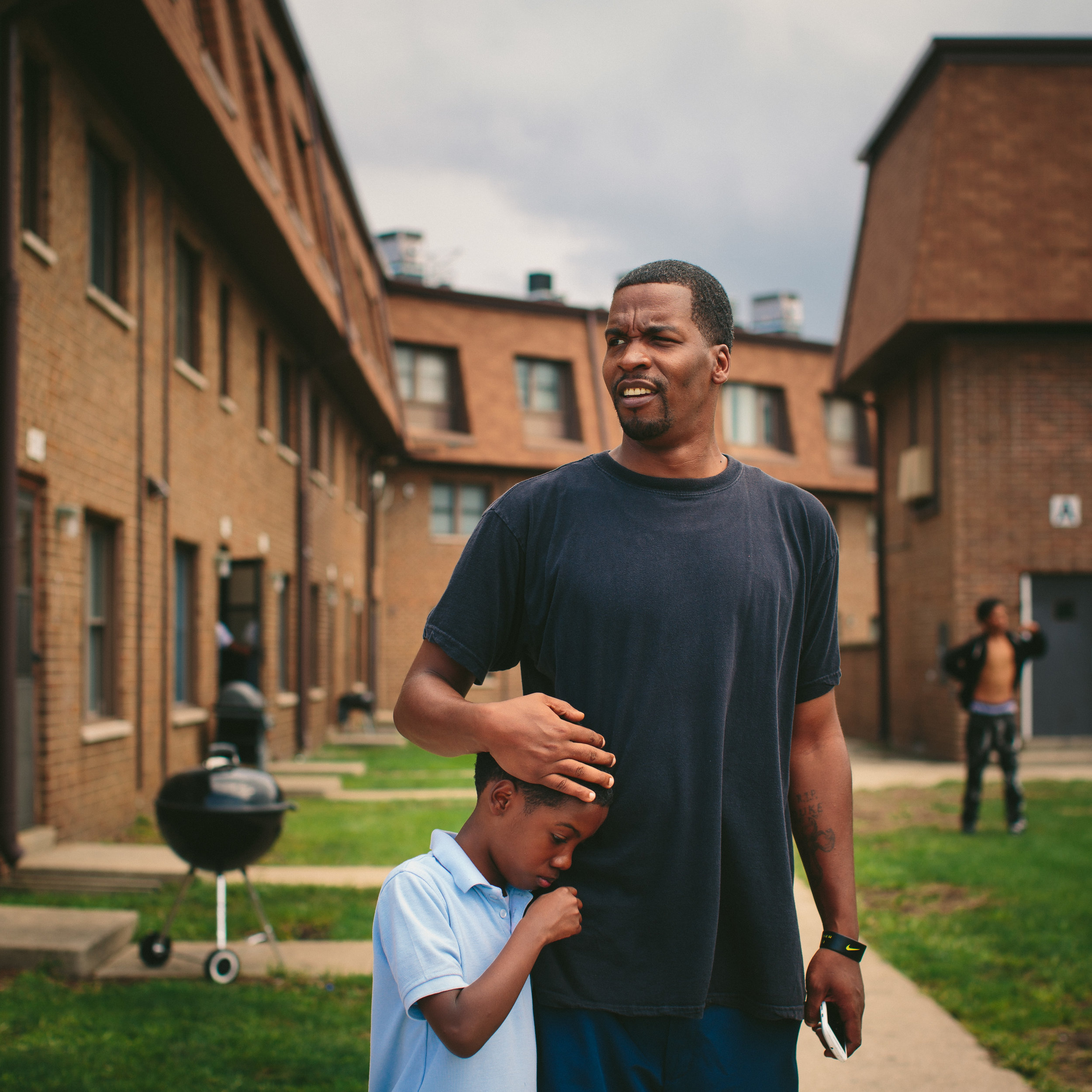 Lamont Anderson embraces his son Lamont Anderson Jr., 8, at the West Calumet Housing Complex. Anderson Jr.'s blood lead levels test results were above the CDC's 5 mg/d threshold for action. After living in the complex for more than a decade, the family moved to Gary, Indiana earlier this summer.