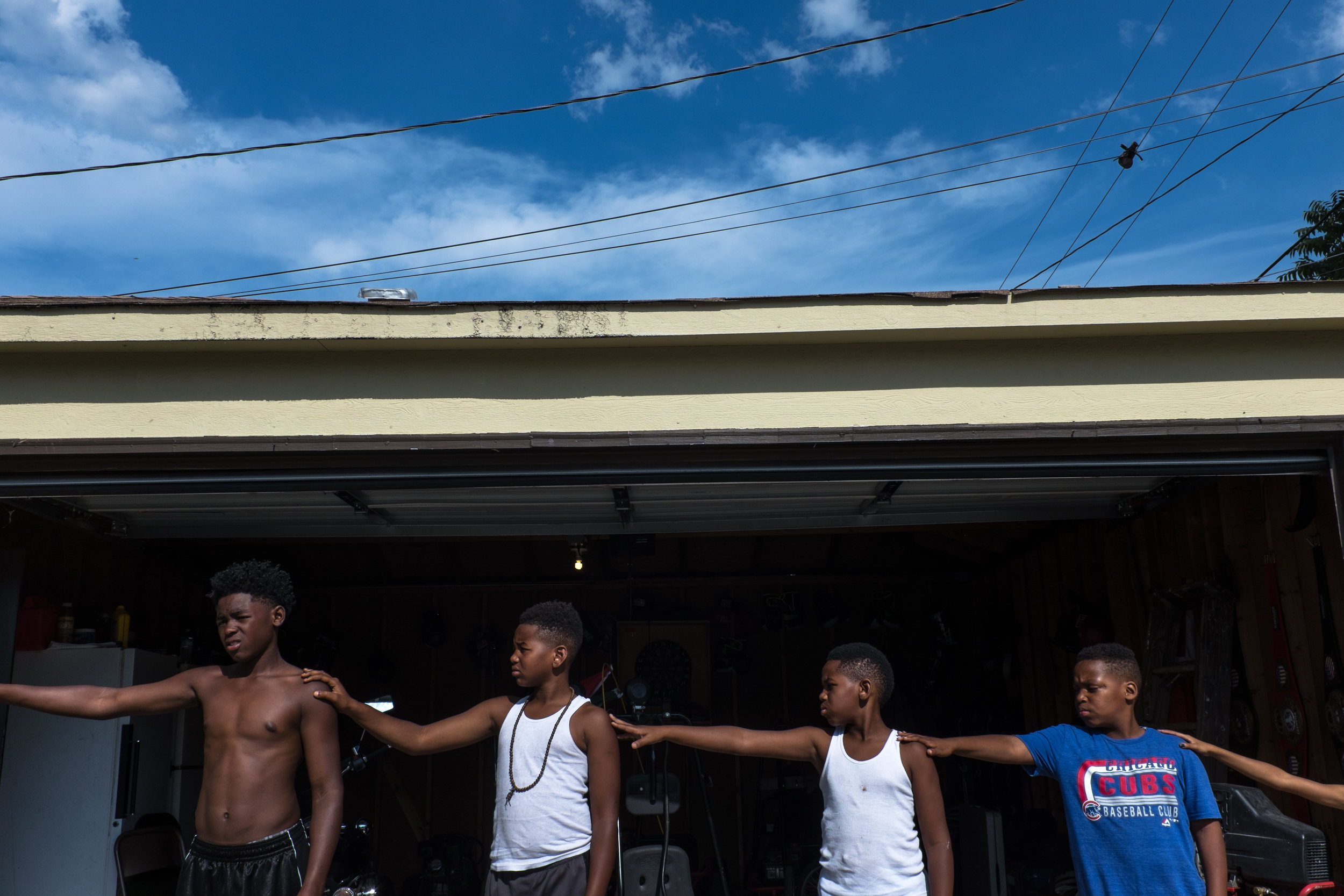 "Members of the North Lawndale Boxing League line up arm-lengths apart before practice on August 9, 2017, in front of Derek Brown's garage. ""I've got all the bad kids in the community, the so-called bad kids. Of course everyone want to learn how to fight especially in this environment. Young men have a harder time because of the trash they walk intoÓ Brown said. But they don't just learn how to fight. They learn how to respect themselves."" (Sebastian Hidalgo)"