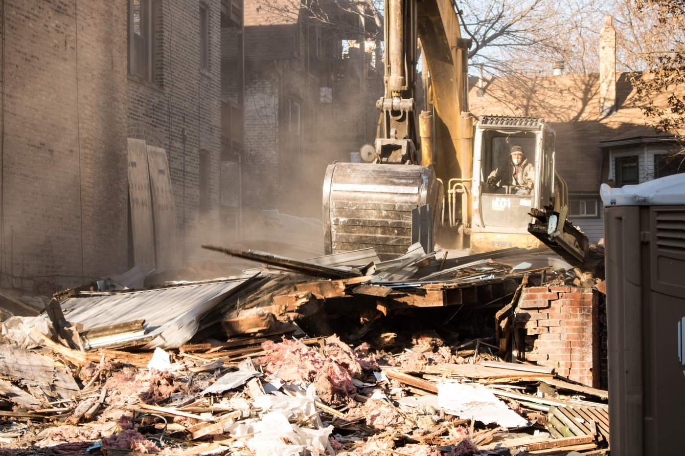 A worker plows through a plume of dust and debris on a demolition site in the Uptown neighborhood. (Photo: Manny Ramos)