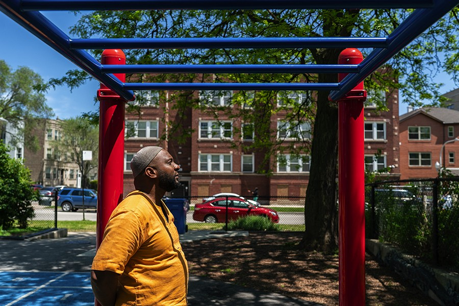 "Aaron ""Haroon"" Garel stands at Huckleberry Park where there used to be a basketball court he says was a frequent gathering point for the Woodlawn community. He lived in the apartment building across the street for several years. (Photo: Max Herman)"