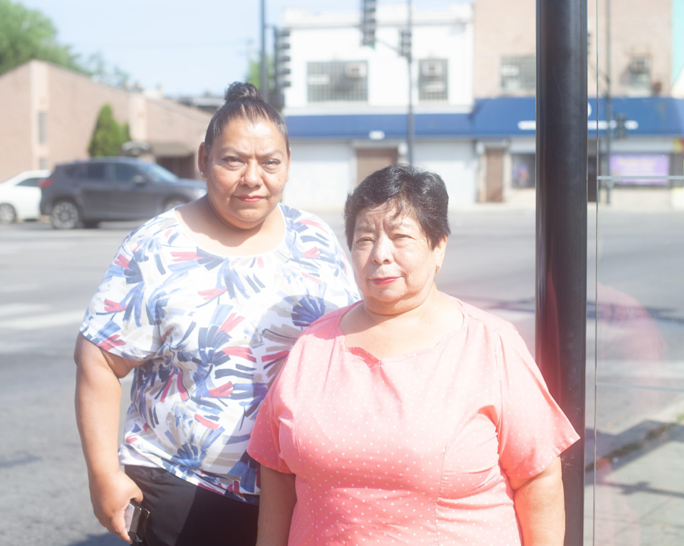 Gloria Hernandez (right) and her daughter wait for the bus home. (Photo: Samantha Cabrera Friend)