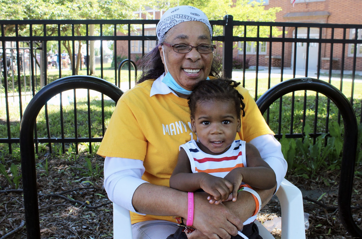 Gertrude Pugh with her great nephew together at the Feed The West Side event. (Photo: Alex Arriaga/City Bureau)