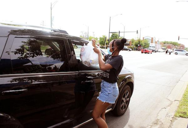 Kyel Brooks hands off groceries at the Oasis on 95th Street food distribution. (Photo: Alex Arriaga/City Bureau)