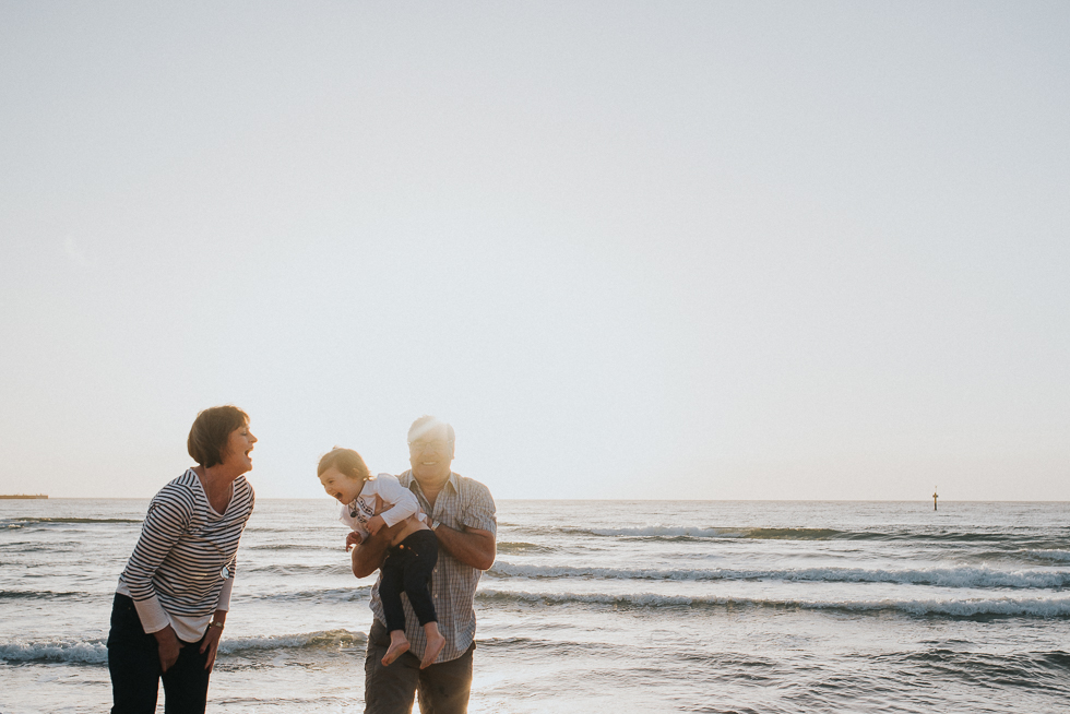 grandparents+playing+with+granddaughter+at+the+beach+in+melbourne+sunset+lifestyle+family+photogfrapher+Jenny+rusby+photography
