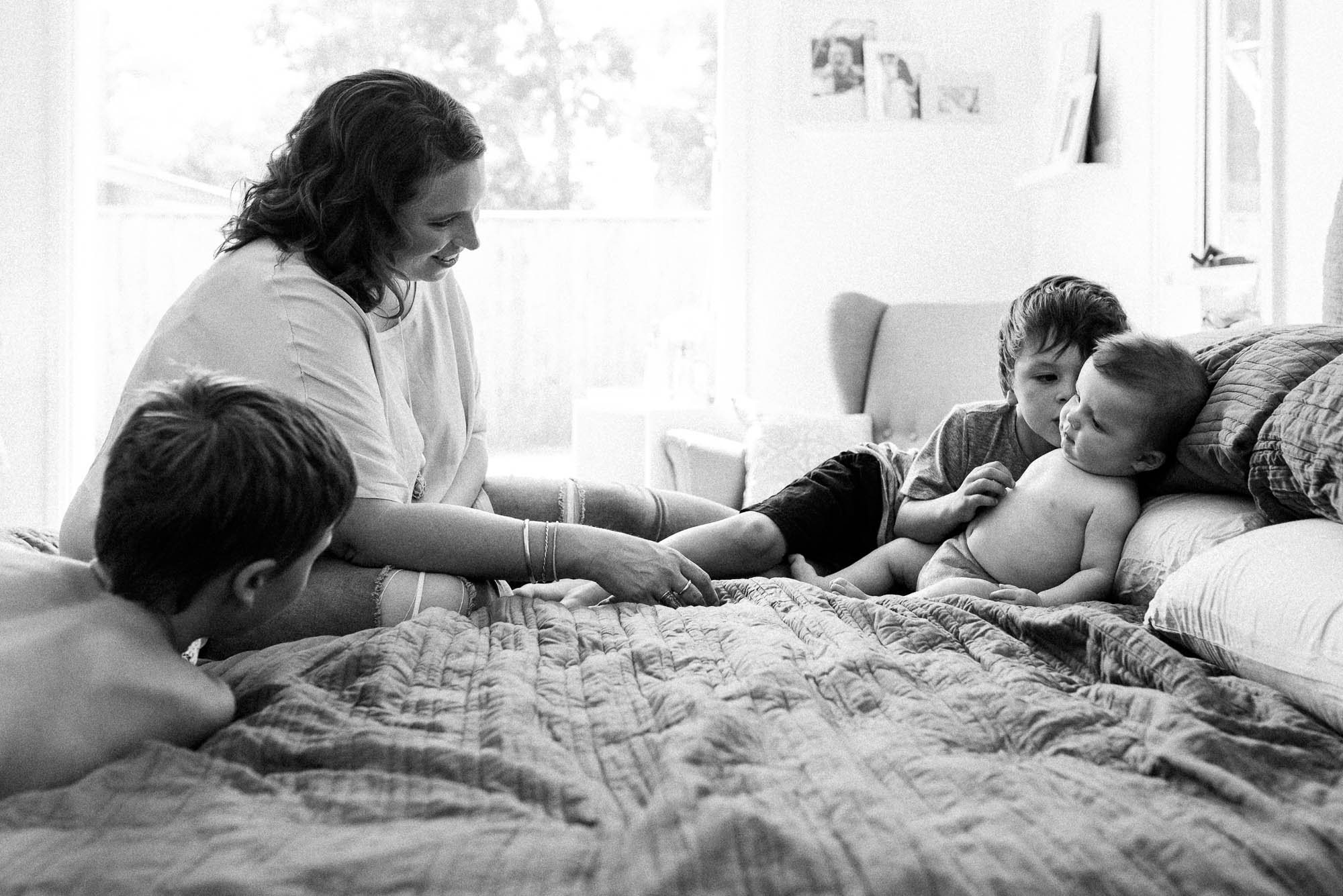 black and white image of mother on bed with four children