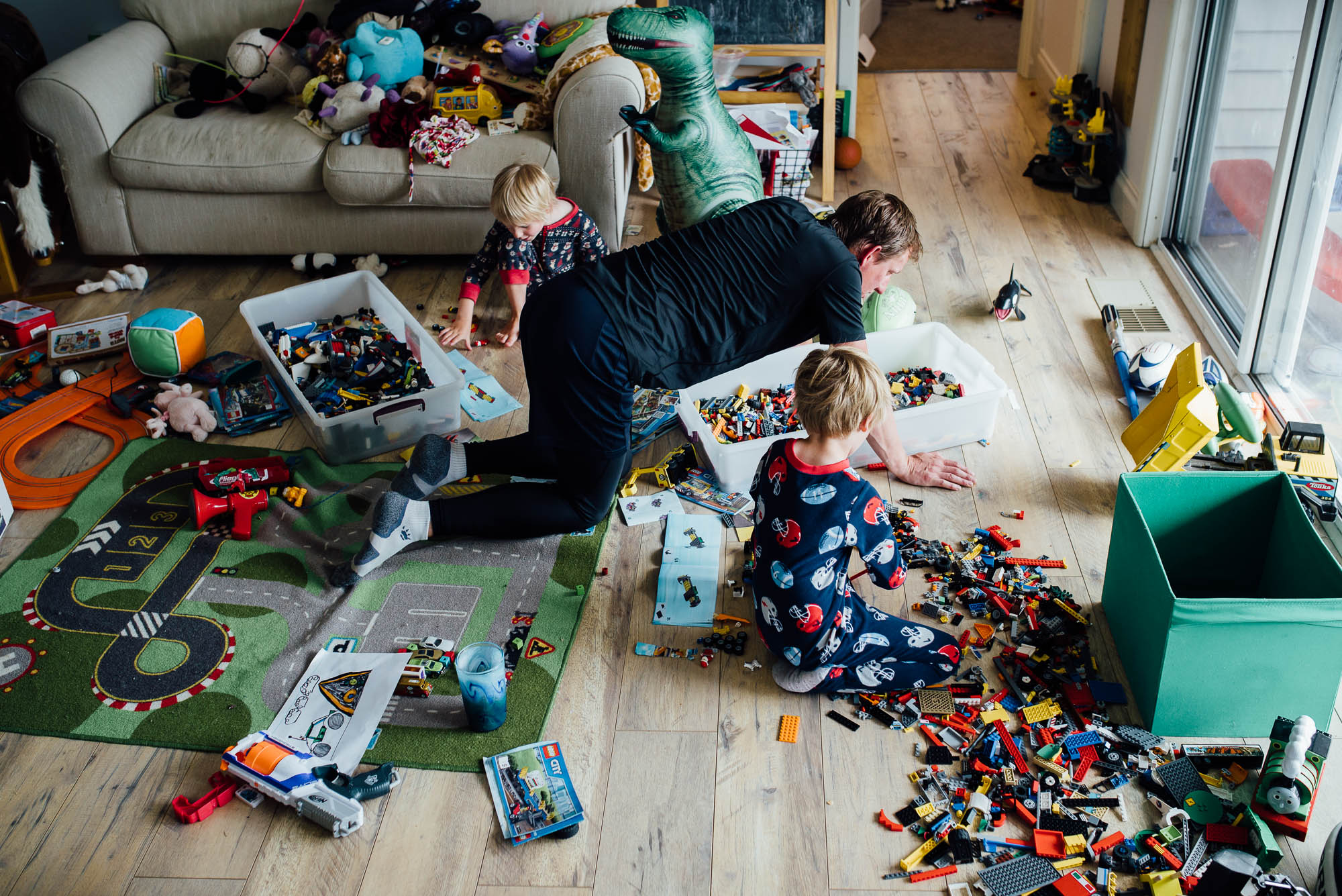messy-playroom-full-of-toys-with-dad-and-two-boys-playing-lego