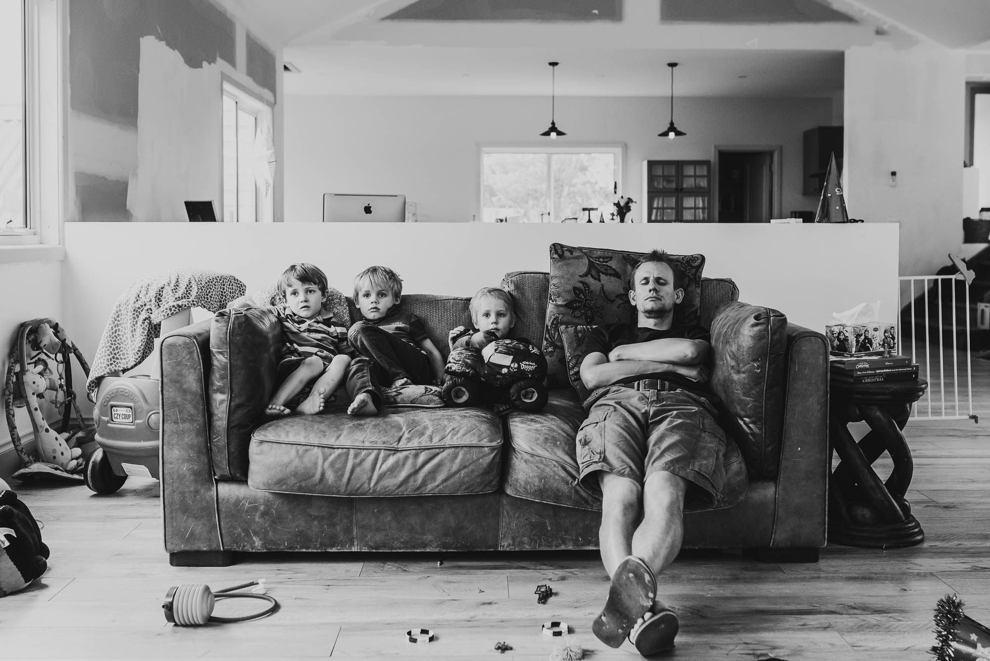 dad-asleep-on-sofa-with-children-awake-next-to-him-and-toys-all-around