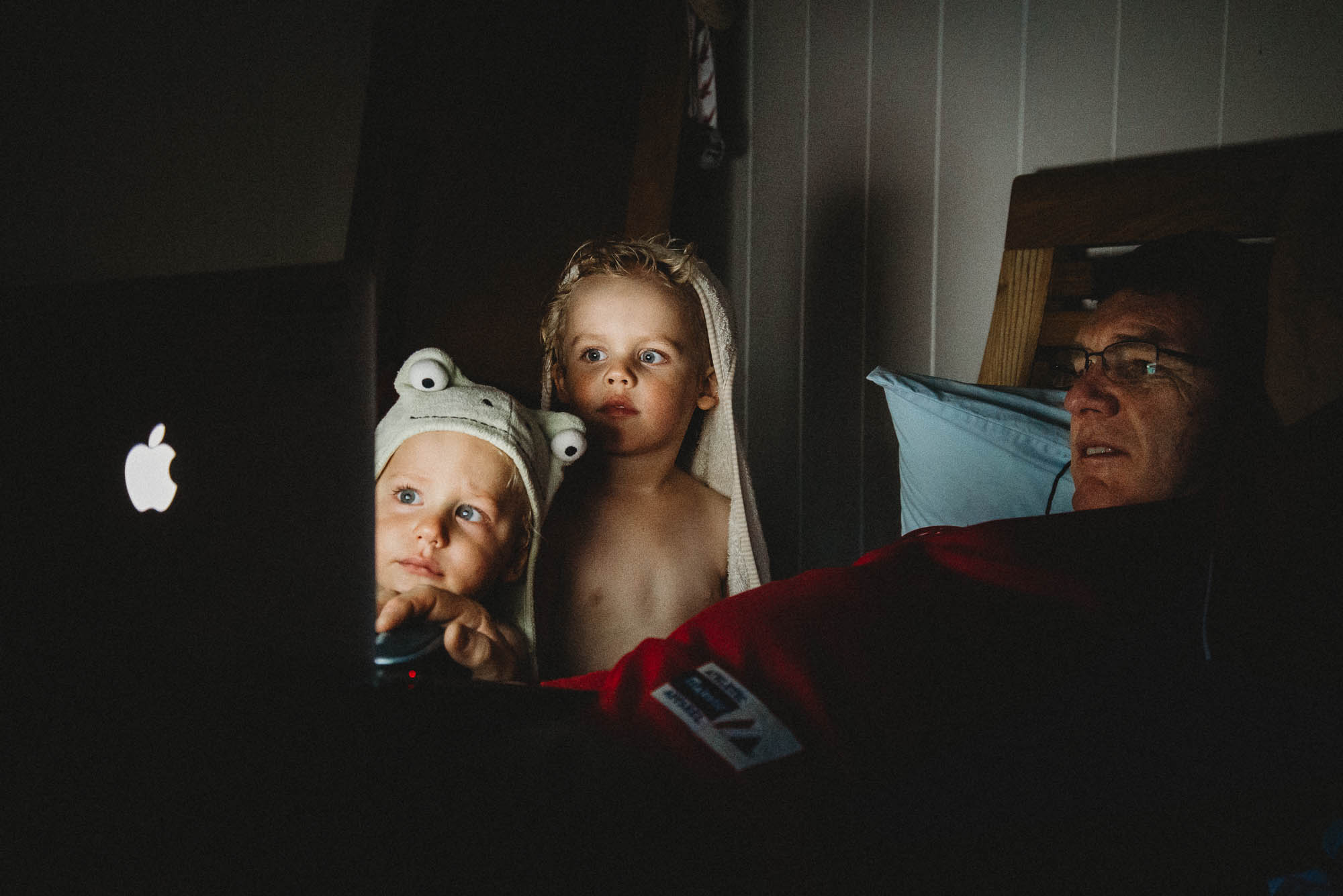 toddlers-watching-computer-in-bed-with-grandpa