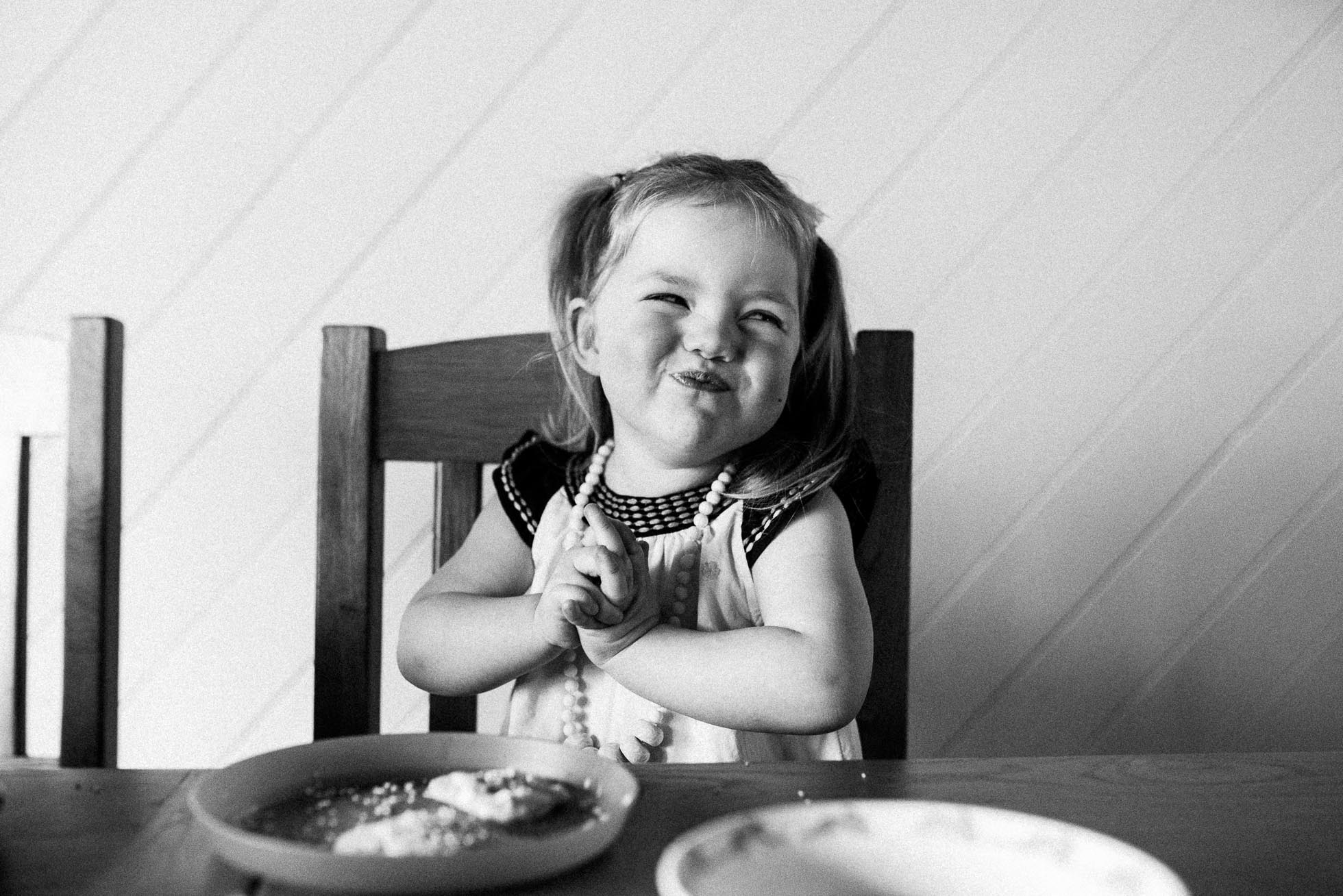 child-smiling-after-eating-cookie-at-kitchen-table-black-and-white-melbourne-family-photographer.jpg