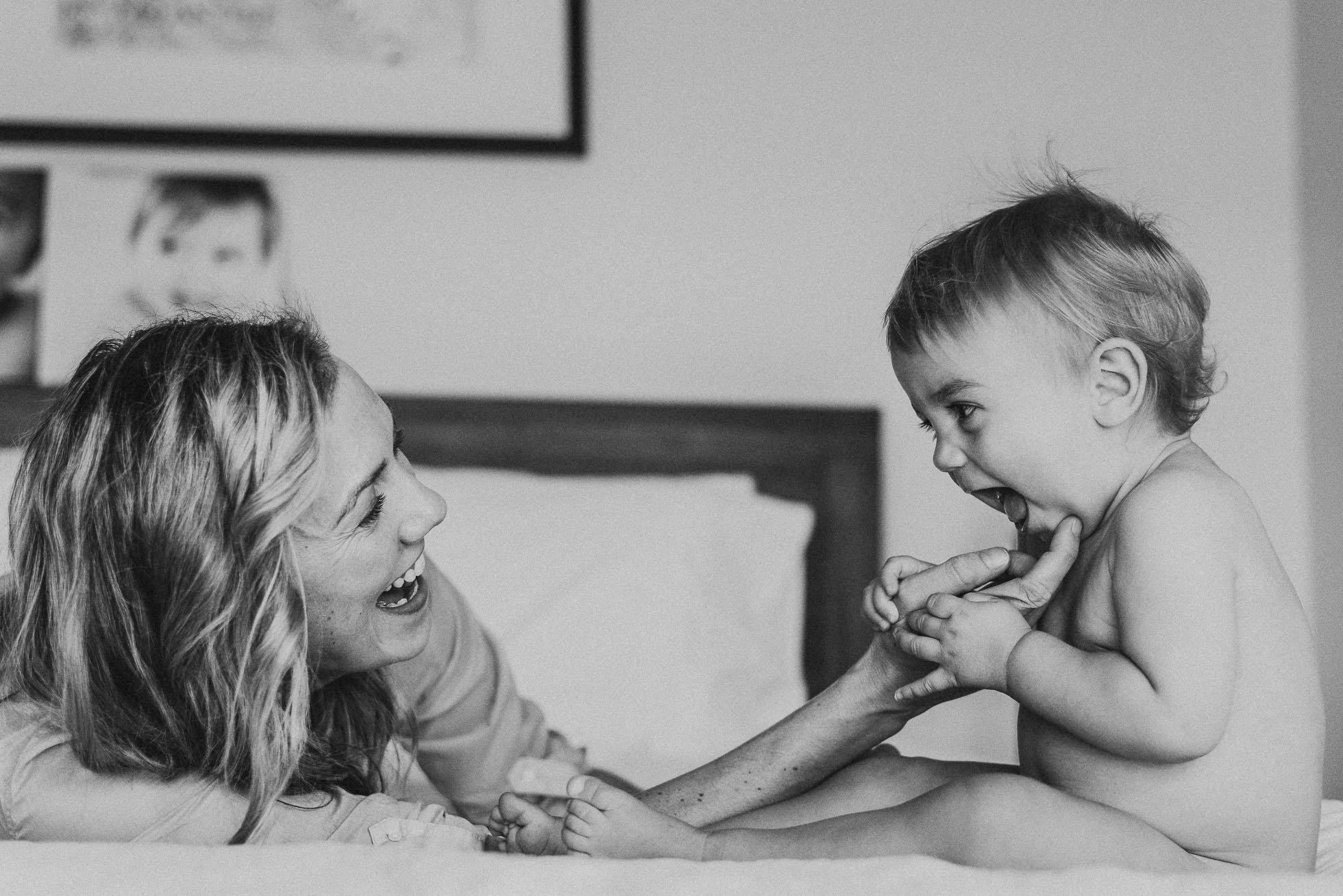 mum-and-toddler-playing-and-smiling-together-on-bed-at-home-melbourne-baby-photographer.jpg