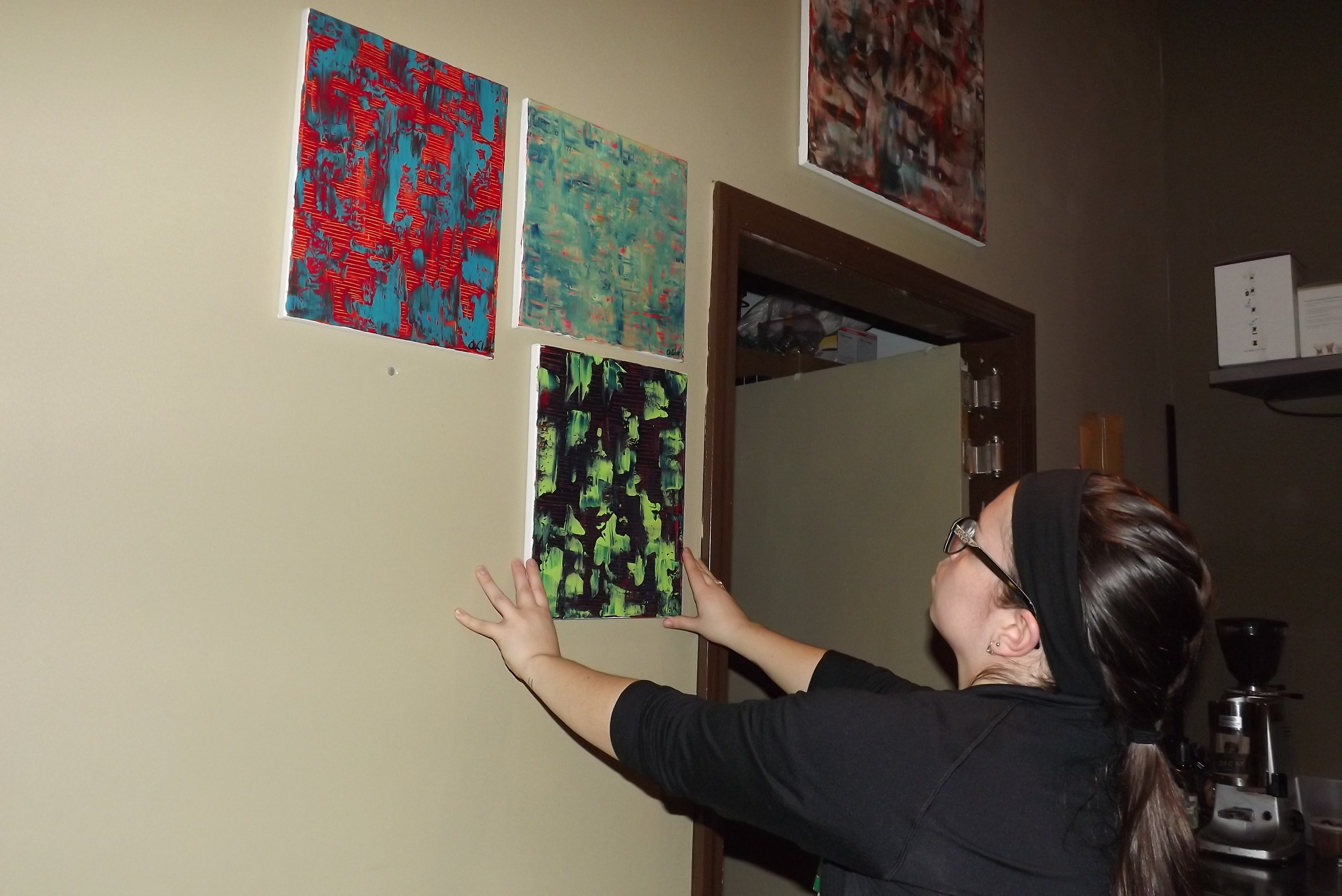 Angelica Clark installing paintings at Cafe Kubal in Eastwood, Syracuse, NY.
