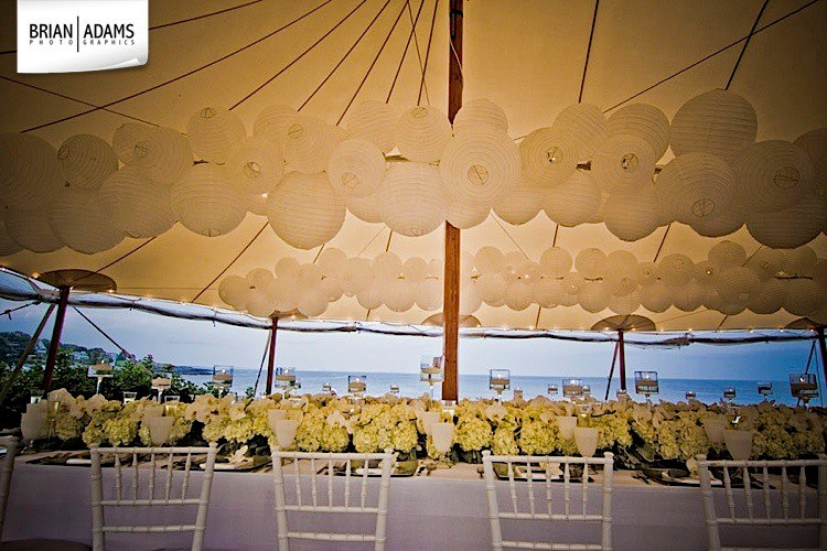 Paper lanterns on cafe strands installed on a long pole to create a cluster of clouds at a private tented wedding in Maine. Image by  Brian Adams Photographics .