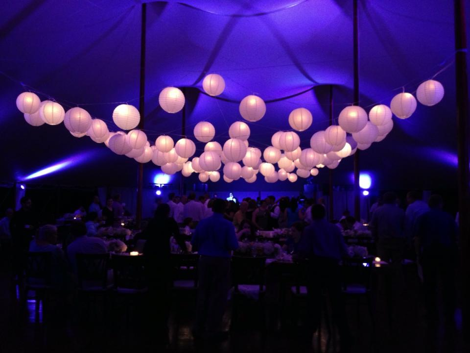 Multi-layered lantern and cafe light installation over a dance floor in a Sperry Tent.