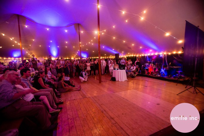 Exposed cafe lights installed throughout a double-wide Sperry Tent, private wedding in Cumberland Foreside Maine. Image by  Emilie Inc .