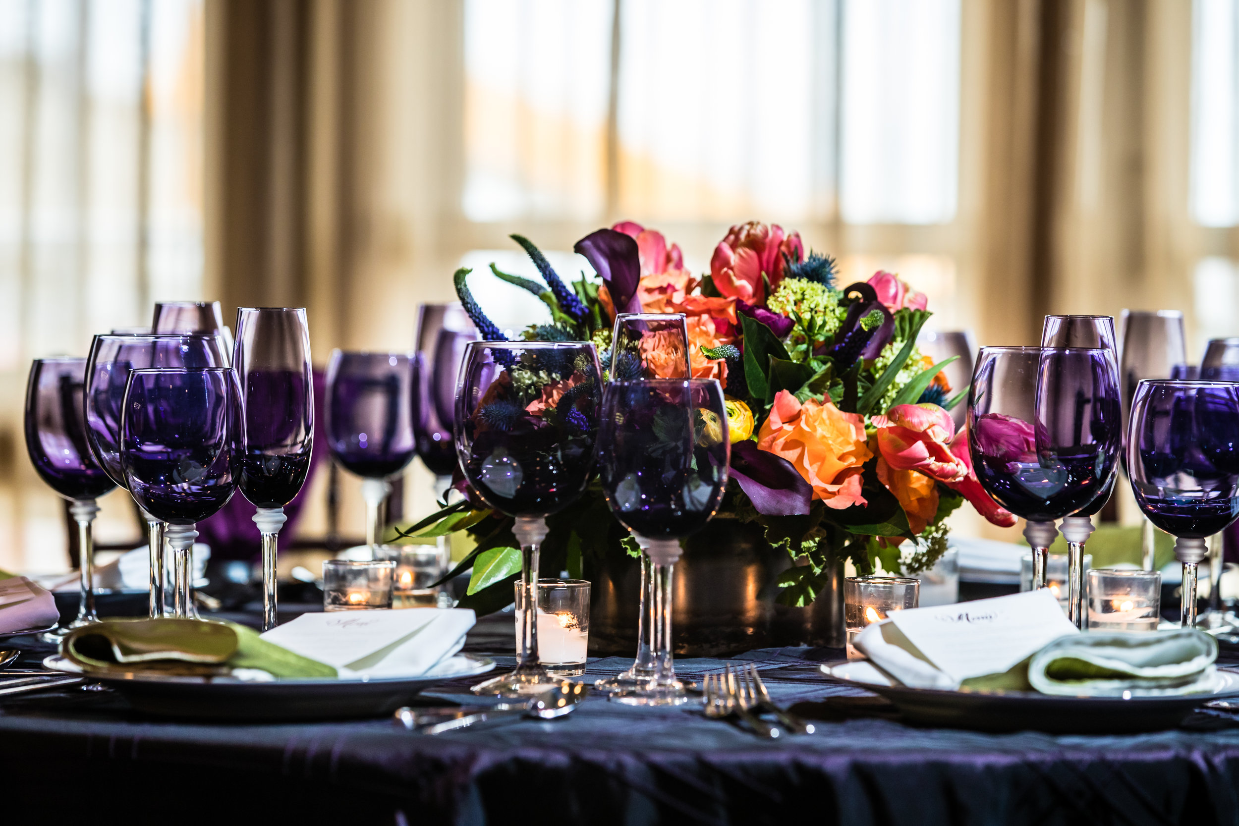 Fall on the ocean. Reception table featuring eggplant linens, green, orange and eggplant florals, and upgraded linens, china, glassware and flatware. Image by  Eric McCallister Photography .