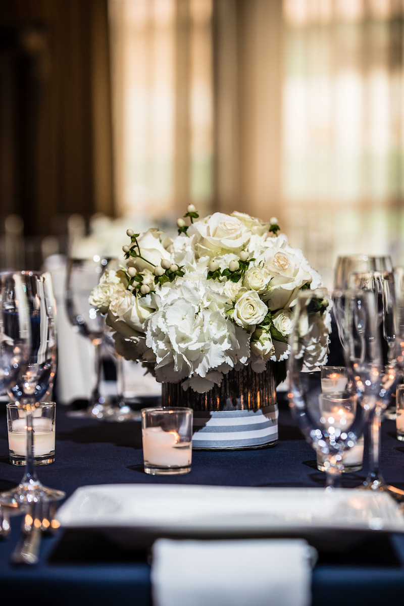 White hydrangea studded with cream vendela roses, white spray roses and white hypericum berries. Photo by  Eric McCallister Photography .