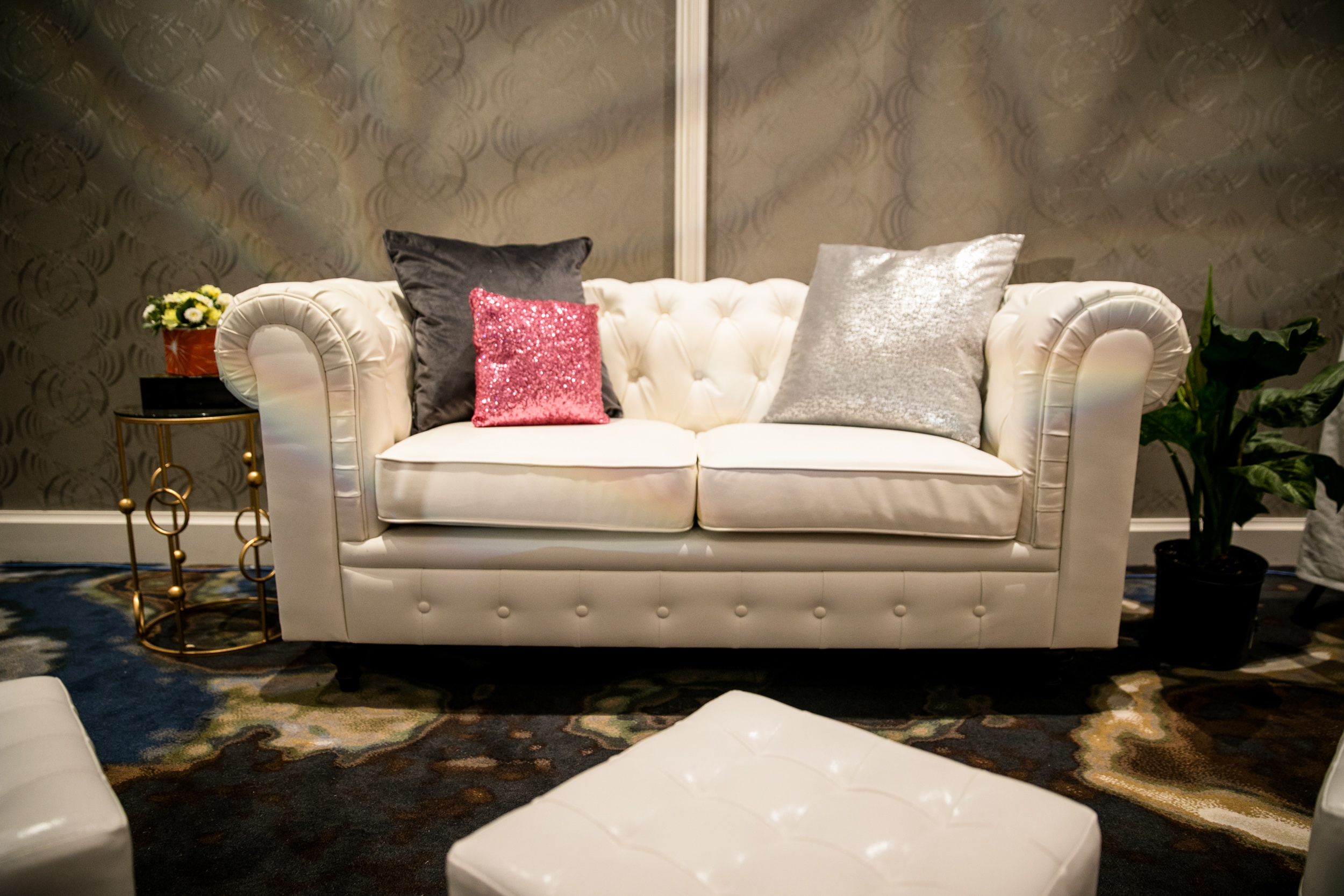 White tufted leather loveseats with dark wooden feet.
