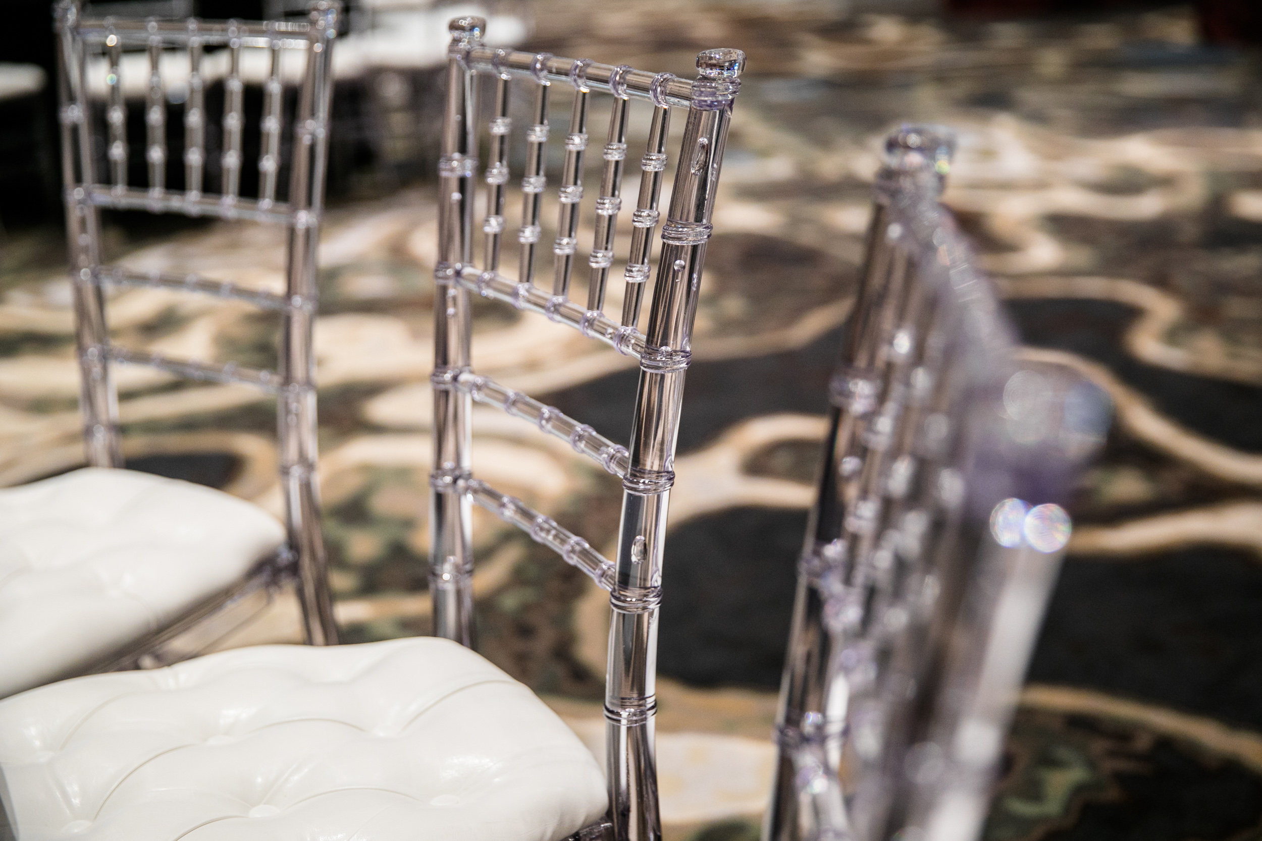 Acrylic clear chiavari chairs.  White leather tufted cushions included.