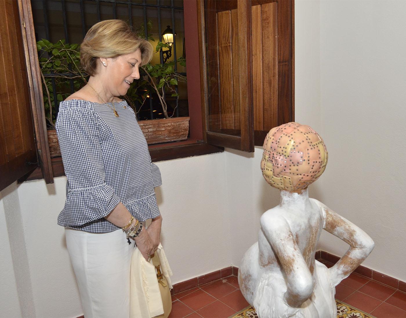 """Mary Carmen Orizondo observa la """"Niña con máscara de piel de muñecas"""" de Jorge Pineda"""
