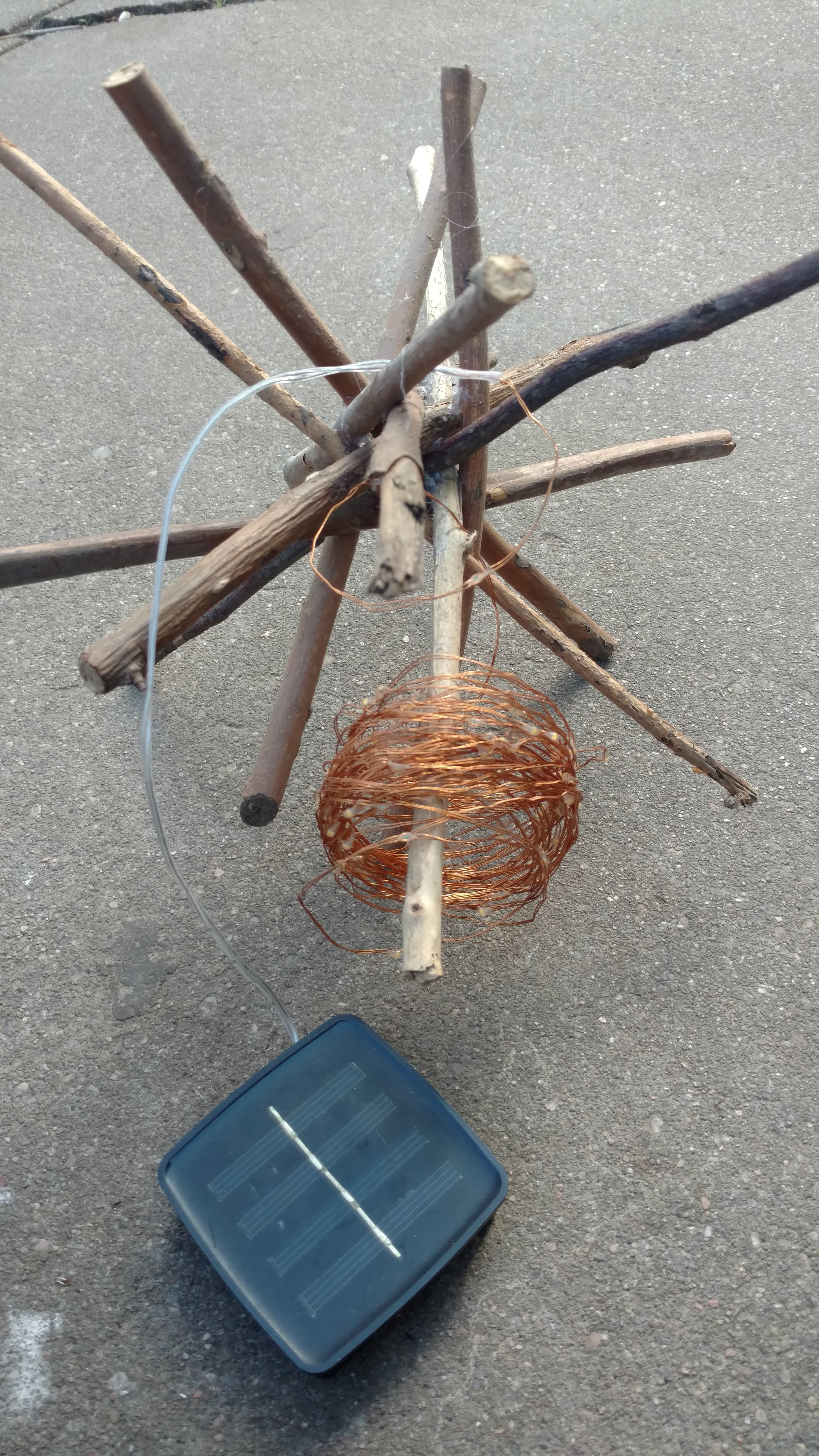 Stick garden art with copper string lights.