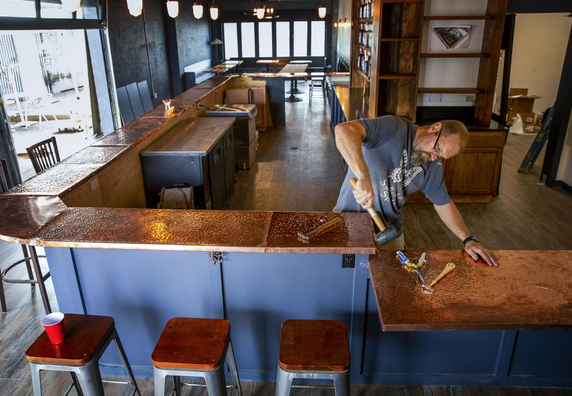 Swallowtail Spirits owner Kevin Barrett works on the bar top in his new retail space and cocktail lounge in Springfield where he will mix a variety of cocktails with his spirits. There is a full bar, outdoor patio and stage for music.