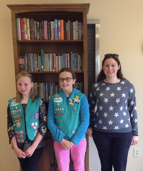 AHP Family Program intern receives bookshelf and books from Junior Girl Scouts.