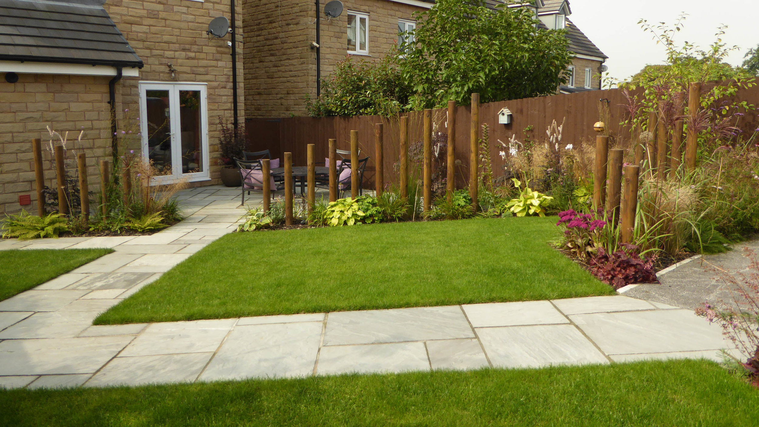 AFTER - New lawn with drainage and planting beds broken by pathway to and from car port.