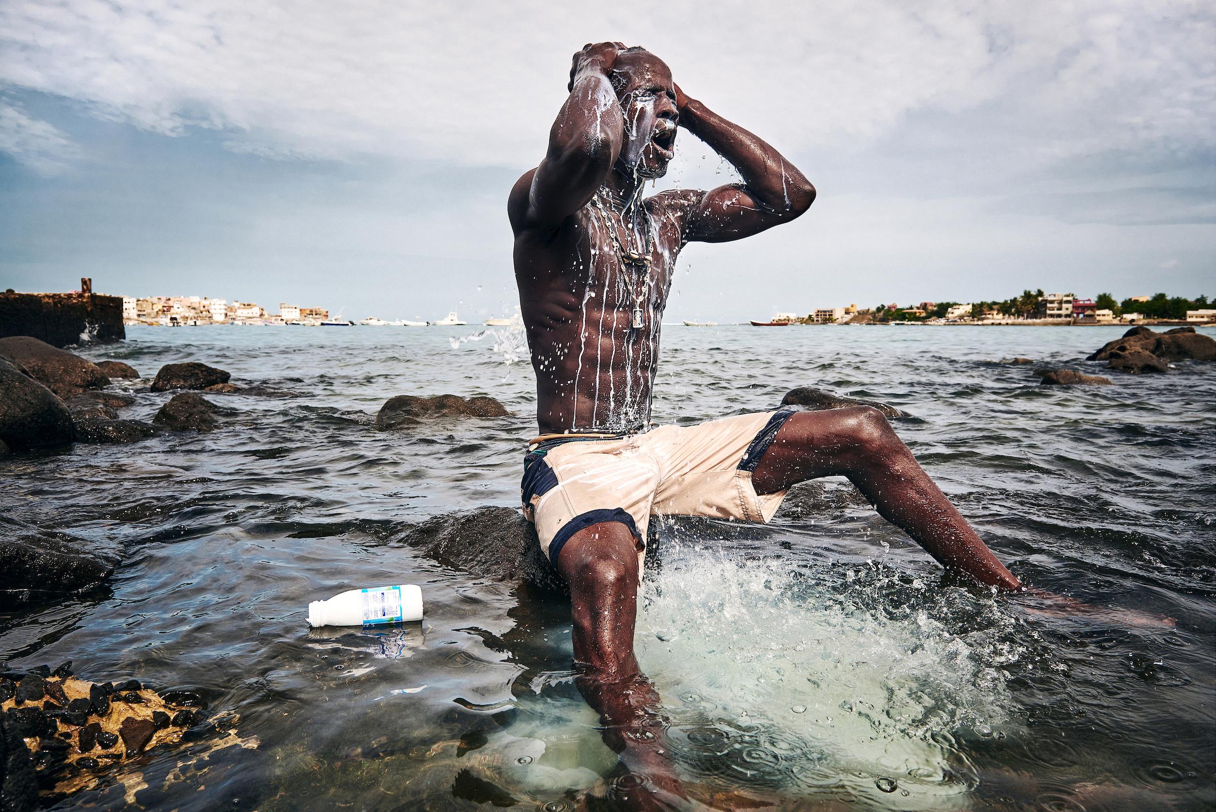 11. August 2015. Kherou Ngor übergiesst seinen Körper im Wasser am Strand von Ngor mit Kuhmilch. Er führt dieses Ritual durch, um sich mit der Kraft eines mächtigen Geistes zu verbinden, der angeblich im Wasser und den Felsen am Ufer des Strands von Ngor lebt.