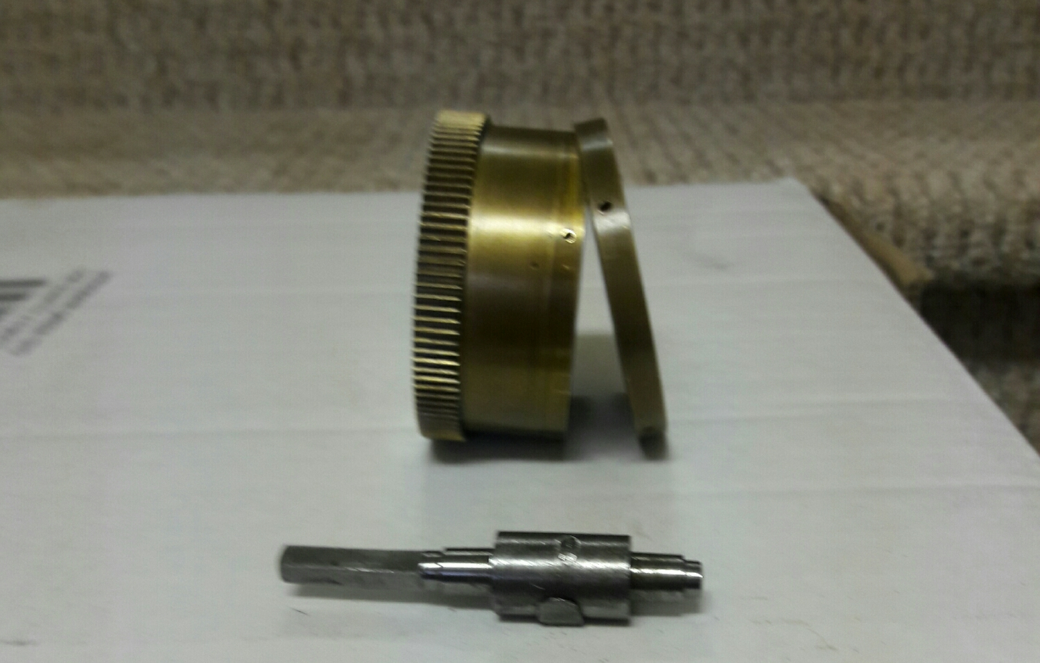 most mainspring barrels have a snap on lid that is flush with the non gear end of the barrel. Here we see a cap that is snapped onto the barrel and secured with 4 tiny screws .