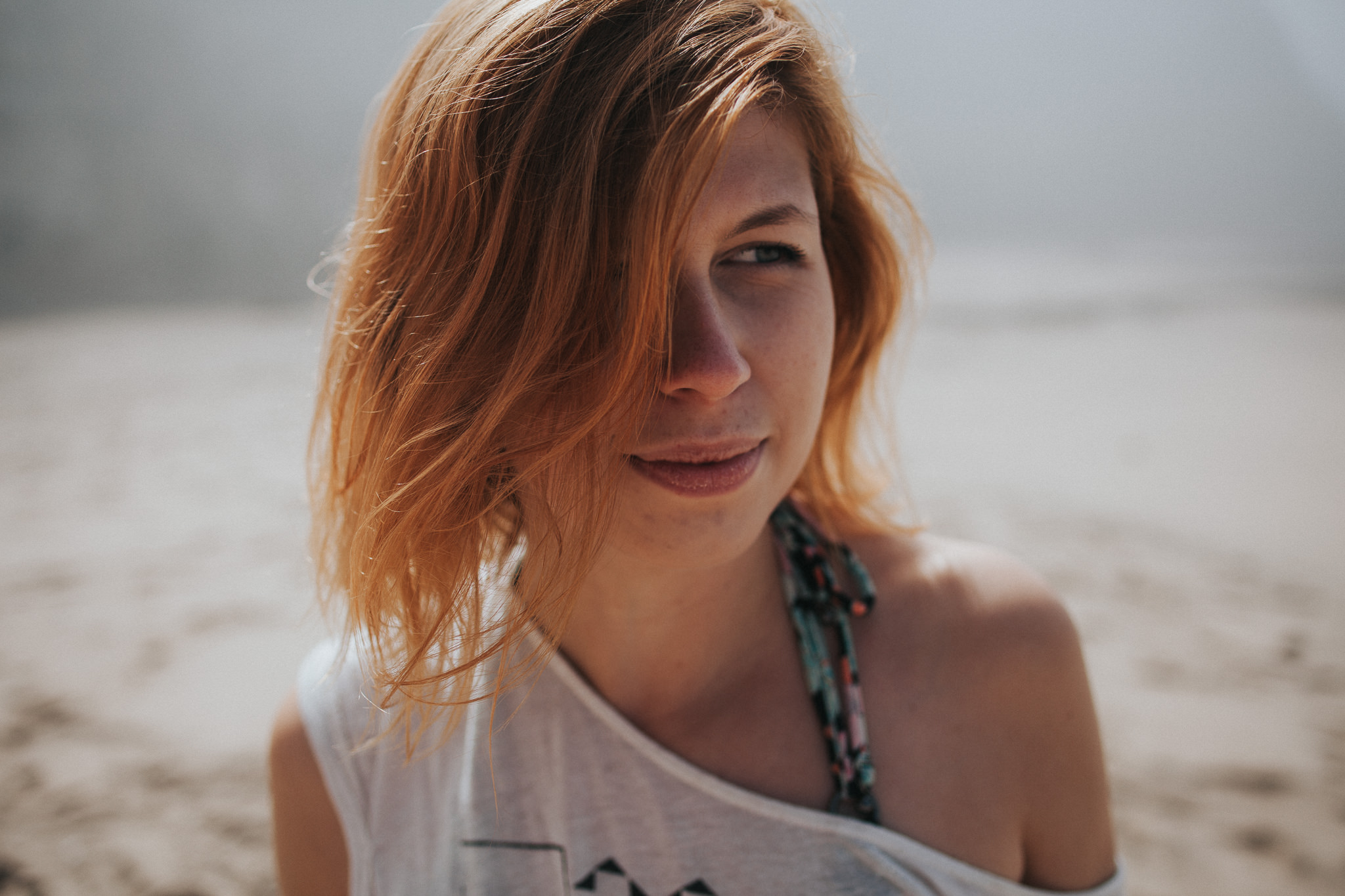 Portrait of a red-haired woman at the beach