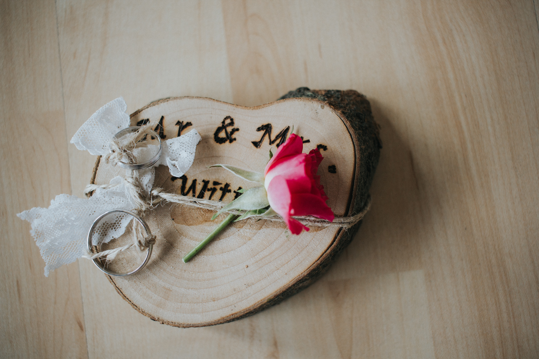 Hochzeitsringe auf Holzscheibe mit Rose