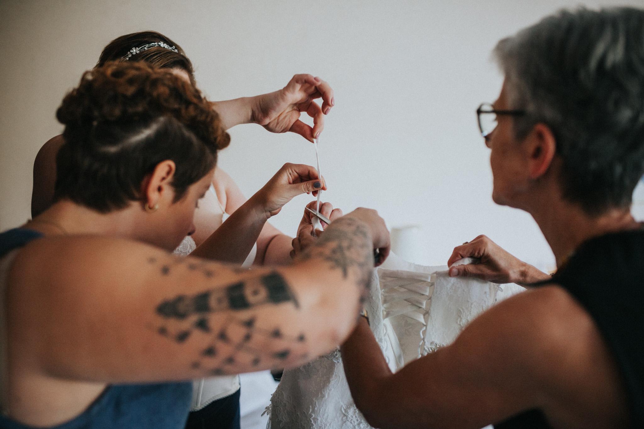 Braut schneidet Träger vom Kleid