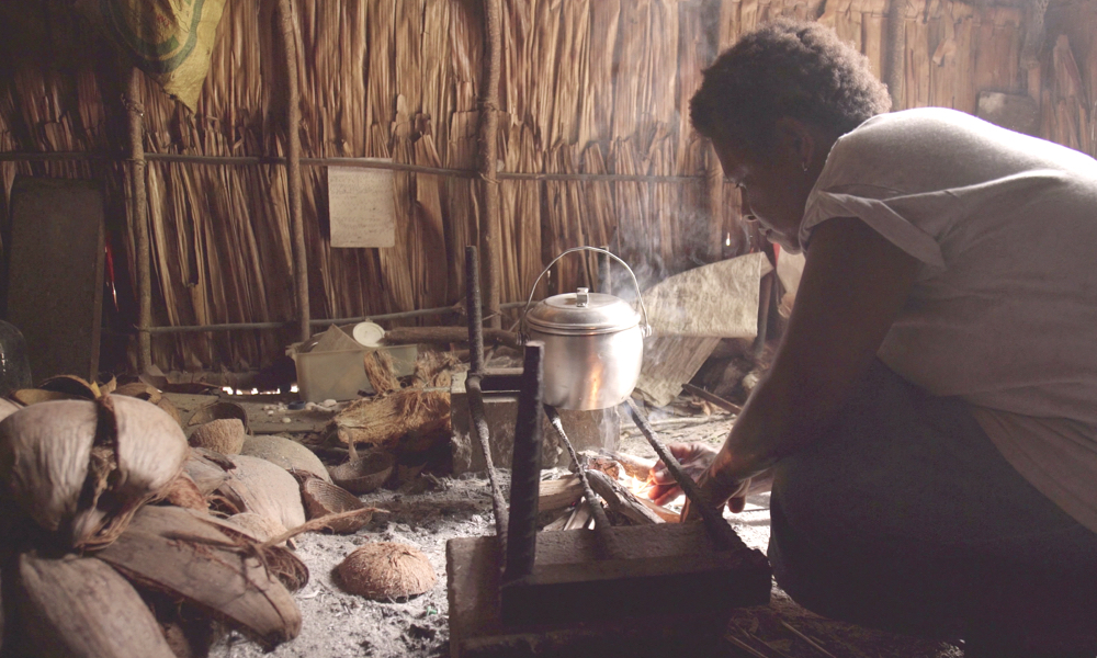 A mother lights the morning fire in her kitchen to 'hotem' water for tea. Piles of coconuts husks tell a story of hard work scrathcing and the walls are a testament to sustainable building materials.