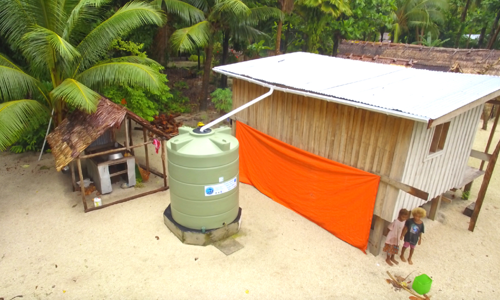 Two pikiniki stand next to their house in Tuwo village in Temotu province.  The Quick Fix phase of the project has provided immediate relief  to communities that were struggling without enough fresh water. The tanks are part of a strategy of diversifying the sources of water so the community has more resilience for the unknowns of the years ahead.