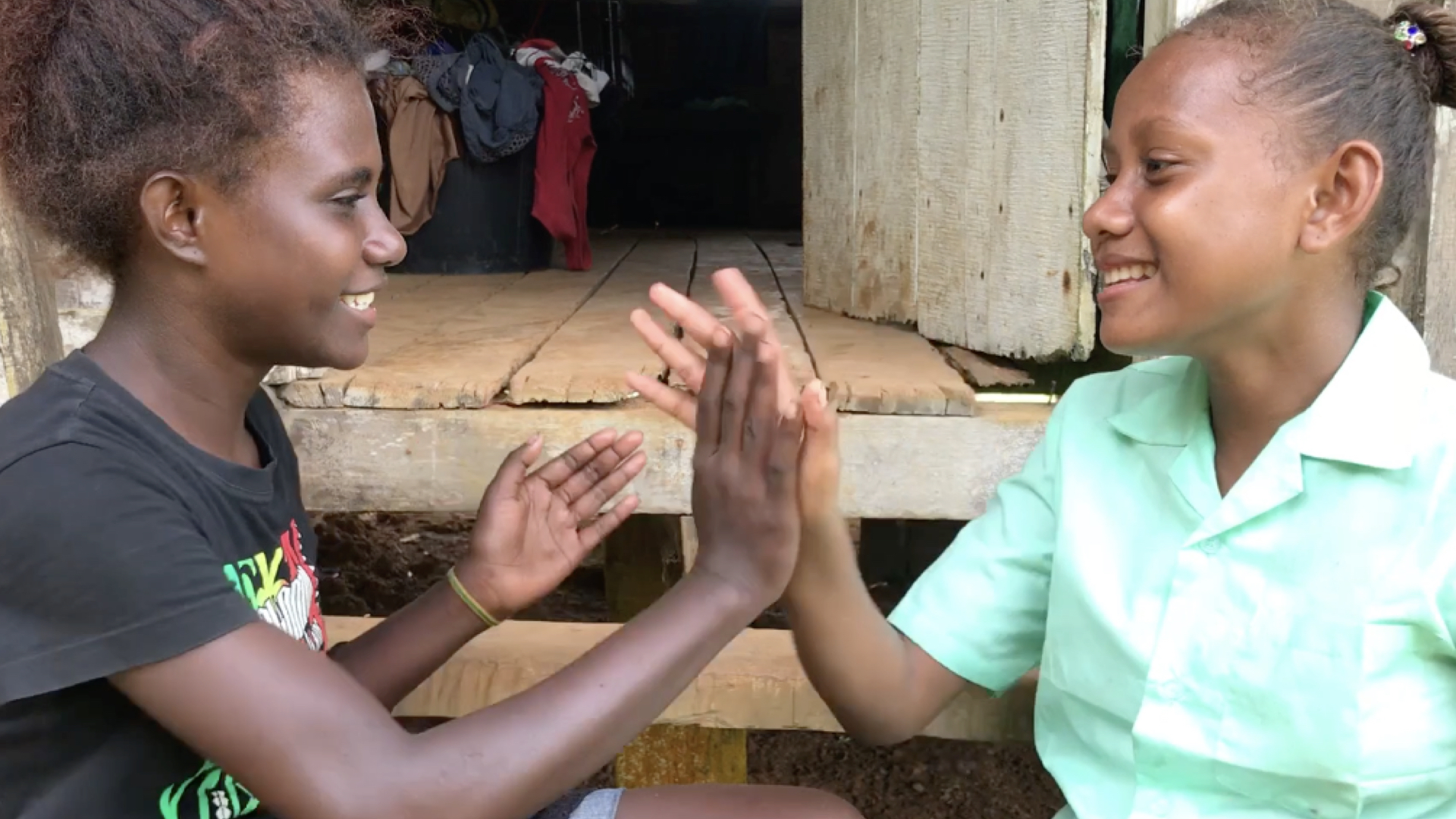 Pamela and her friend take a break from collecting water and chopping firewood to play a game on the steps of her family home. A rich culture of songs and stories is woven into the fabric of Solomons life.