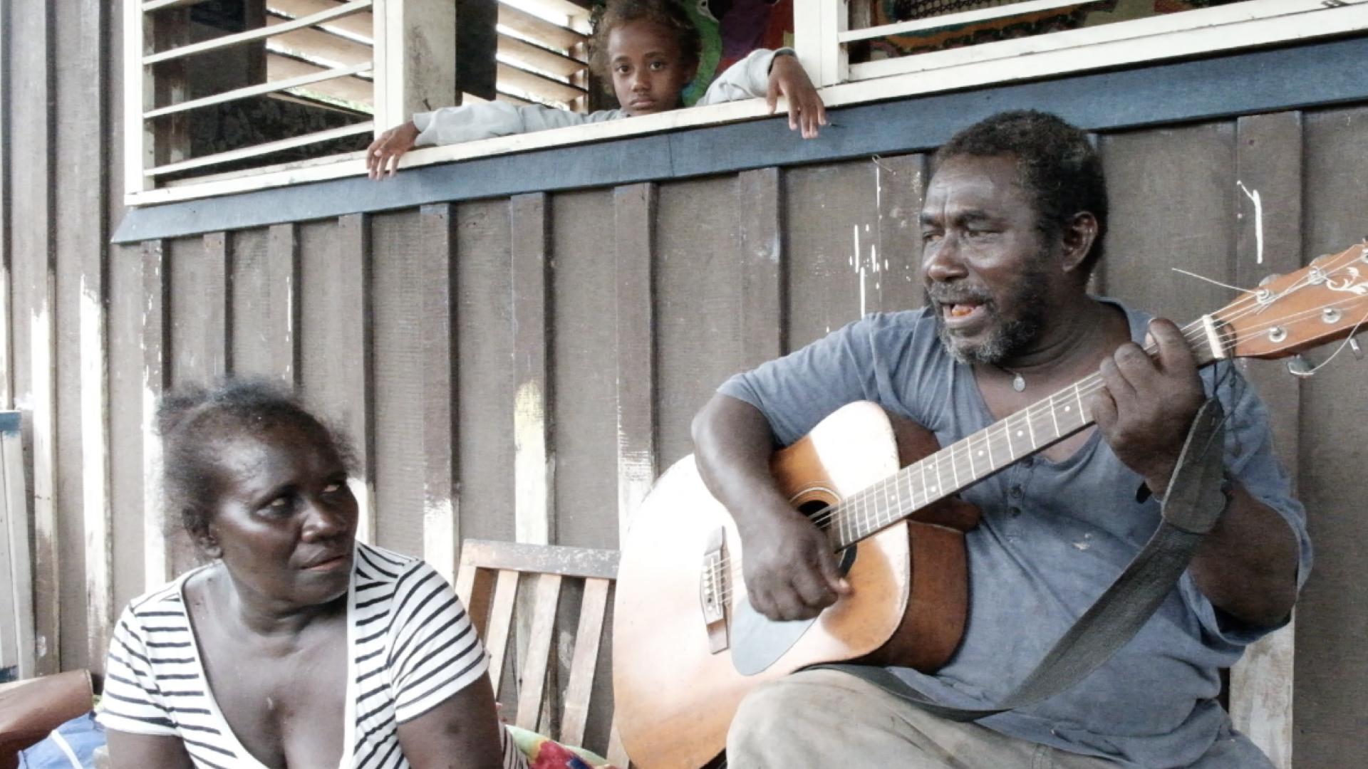 Jimmy's granddaughter looks at the camera as he plays another duet with his wife. Jimmy says climate change adaptation is about balancing the inequalities and addressing the injustices his people are facing as a result of industrial countries carbon emissions.