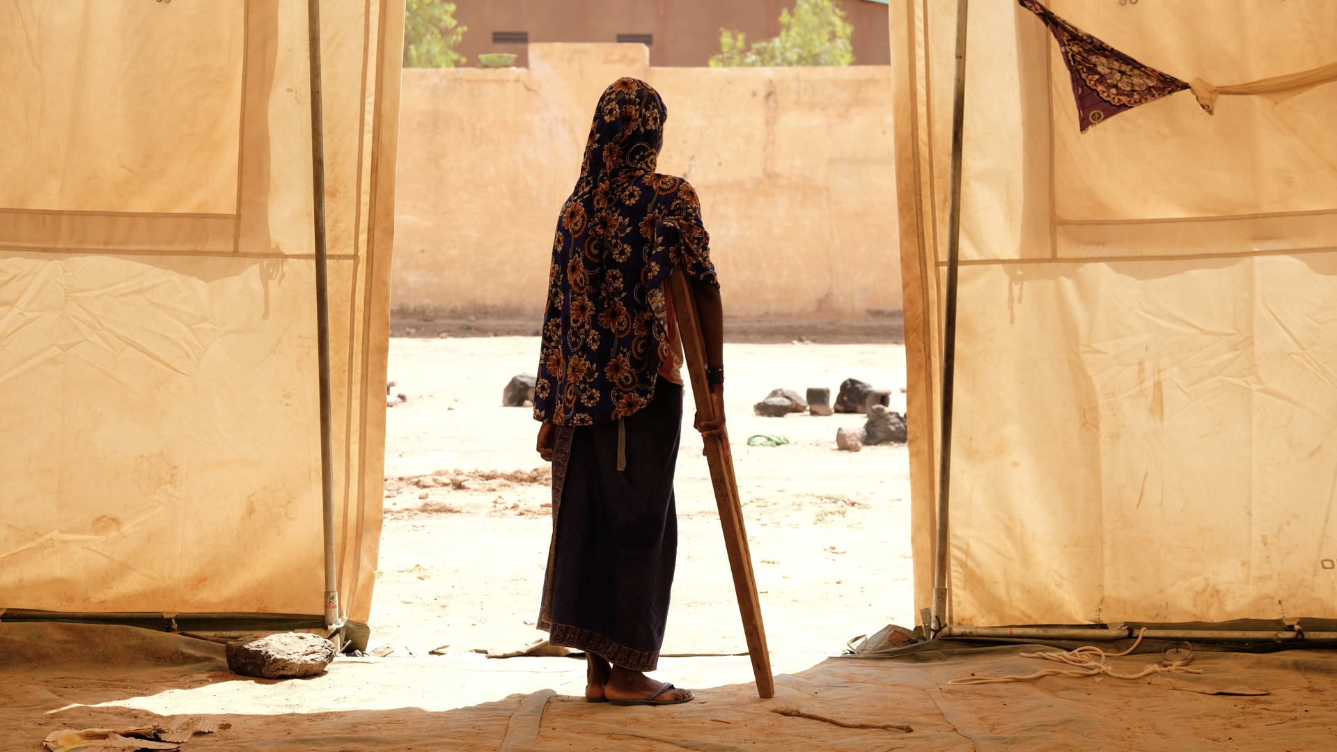 Awa stands outside the door of the tent of a temporary school in a camp outside of Mopti. Her mother was killed in an attack on her village and she was shot in the leg. She's recovering in the safety of the camp but says she's still in pain and struggles walking with the crutch her brother made for her.