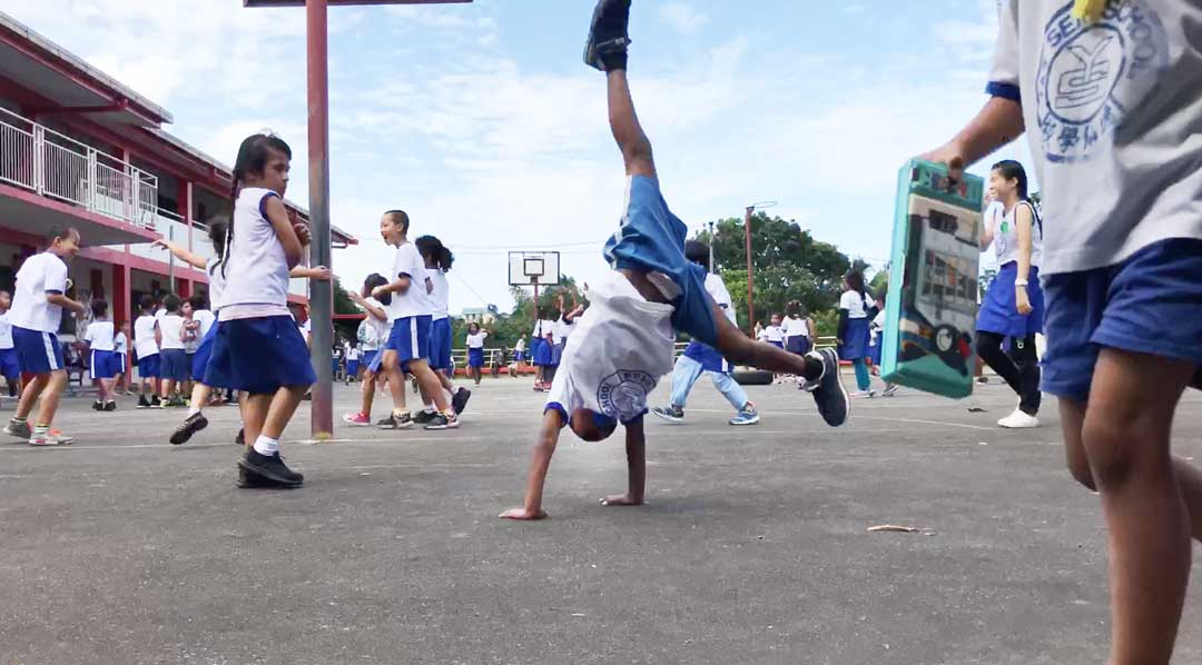 A boy does a cartwheel in the schoolyard at Yet Sen Primary School in Fiji's capital city of Suva. Government prioritization of education is helping more children across the country get to school and prepare for the future. Despite the progress, more remains to be done to ensure Fijians children get the right nutrition and support during the early years that will help them thrive.
