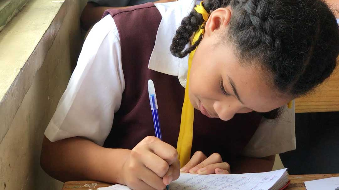 A girl leans over her notebook and does her work with care and attention at Tonga High School in the capital of Nuku'alofa. The school is one of the nation's best and students have to work hard to excel in this competitive secondary school if they want to win honors and get a chance to study overseas.
