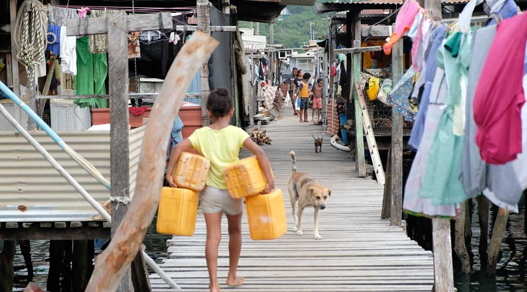 A young girl carries a jumble of water containers to the standpipe at the end of the pier where she lives in Hanuabada village just outside Port Moresby in Papua New Guinea. The water service is intermittent and families have to keep their bidon in a queue waiting for a couple of hours a day when they can get the daily supply. Sometimes not everyone gets enough so neighbors have to share and make due with water rations.