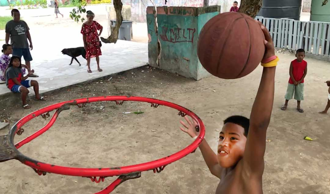 A boy goes in for a slam dunk on an improvised basketball court under a tree outside his home in Majuro. Basketball is popular as a result of American influence, but the more corrosive influence of the American diet of imported foods has taken a toll on the health of young people in the Marshall Islands. The Early Childhood Development Program will increase support for nutrition programs and aims to improve child health across the country.