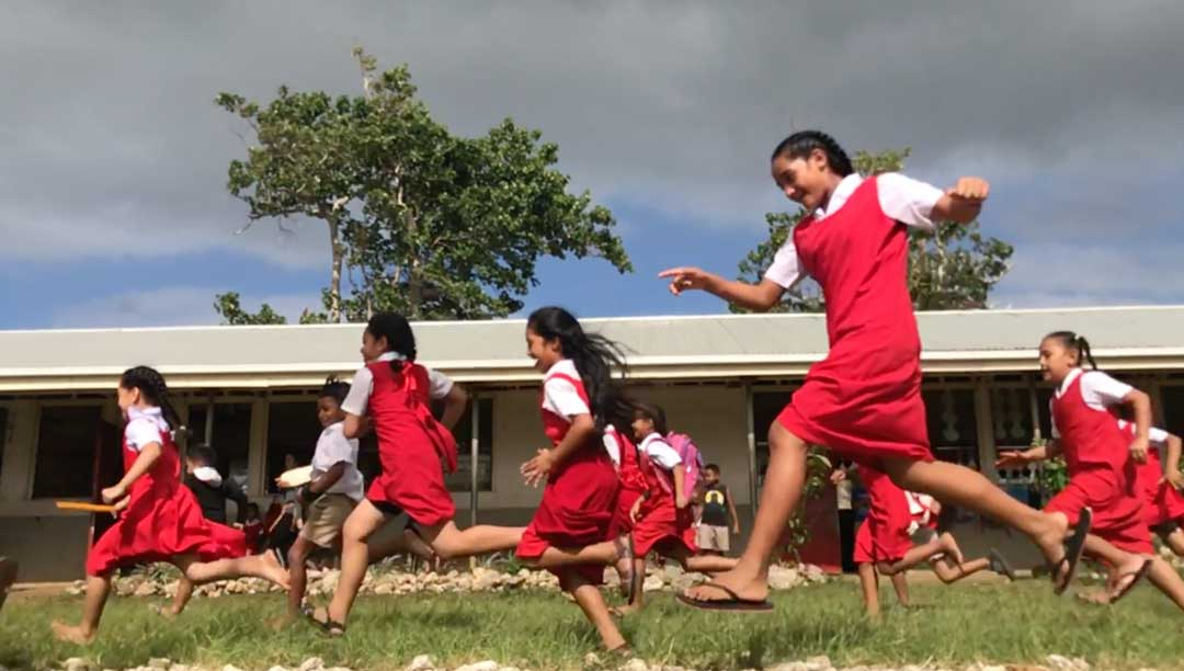 A streak of red rushes past the camera from the school uniforms of Tongan girls on the playground of their primary school in Nuku'alofa. Education in the Kingdom of Tonga has long been a priority, but gaps in the quality of education will require a 'whole of government' approach to support children with health care, nutrition and well resourced schools.