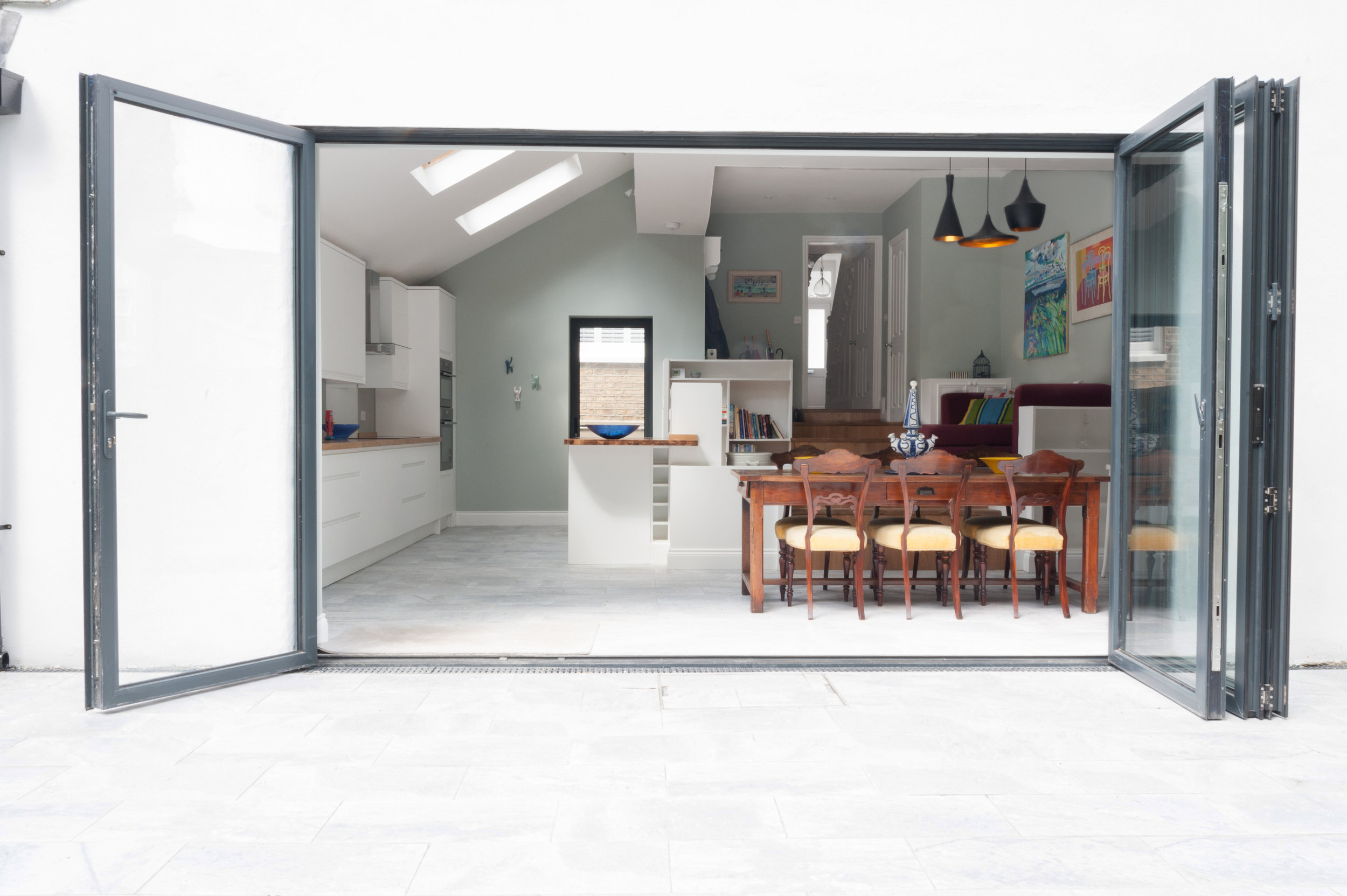View from garden through bifold doors into large kitchen, dining, family room.