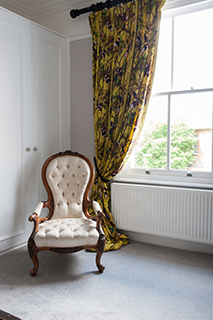 Kingston master bedroom with chair and curtain copy.jpg